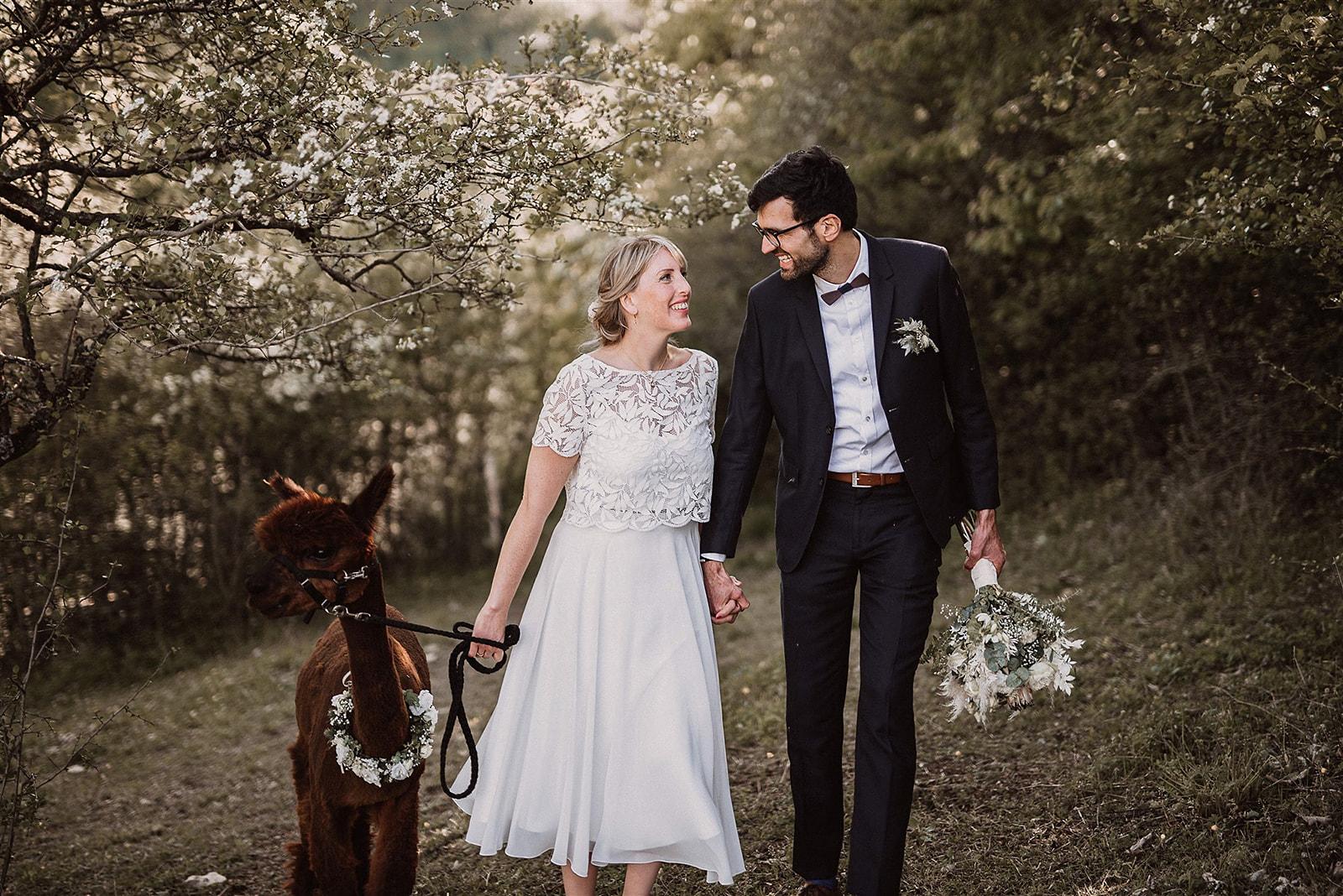 Brautpaar lachend und händchenhaltend vor blühenden Bäumen. Braut mit weißem Brautkleid-Zweiteiler: Chiffonrock in Wadenlänge und kurzärmeligem Spitzentop mit Blättermuster, Bräutigam mit dunklem Anzug, Brautstrauss haltend