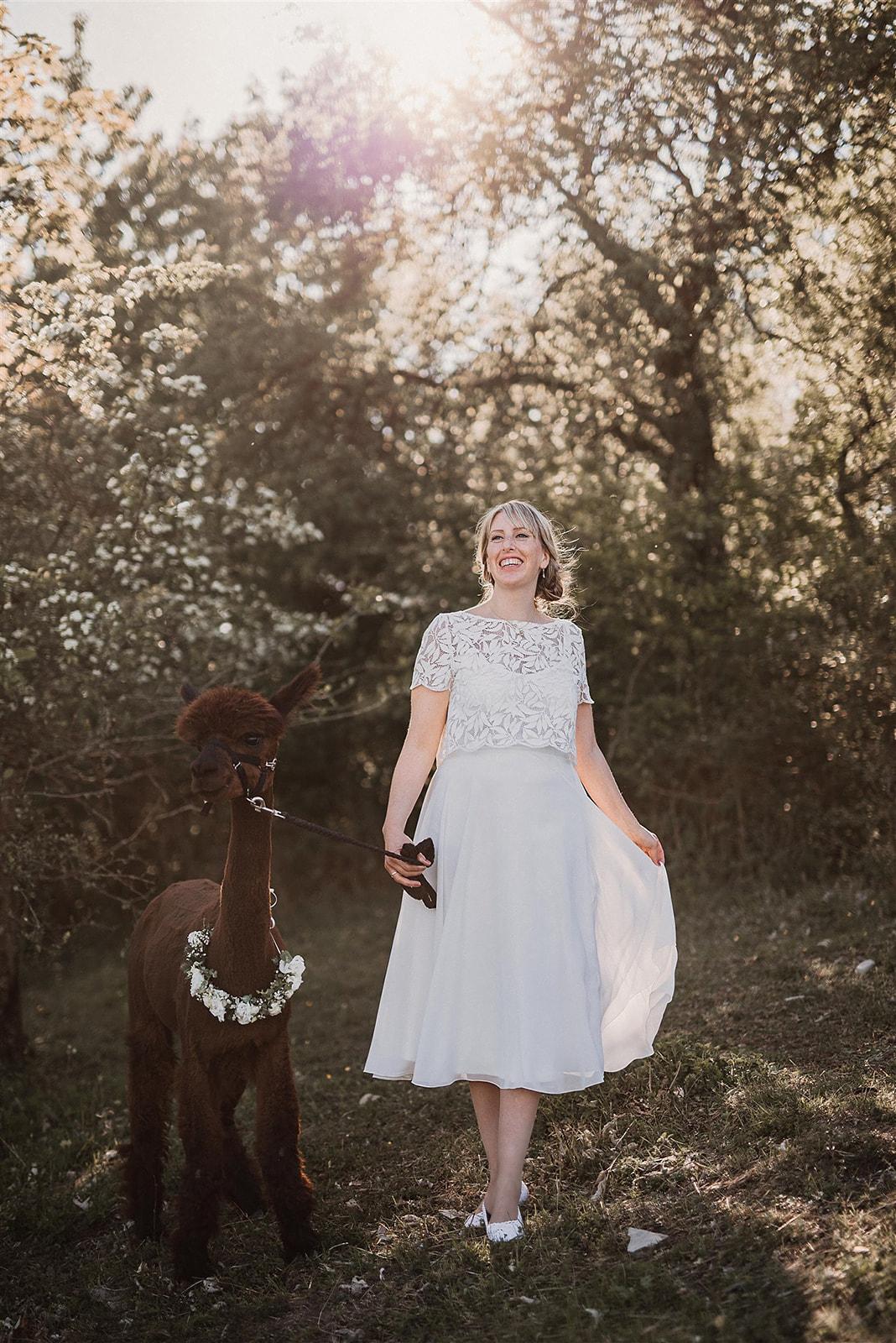 Braut mit Kurzarmtop mit Boho-Muster und Midi-Rock aus Chiffon vor blühenden Bäumen, lachend