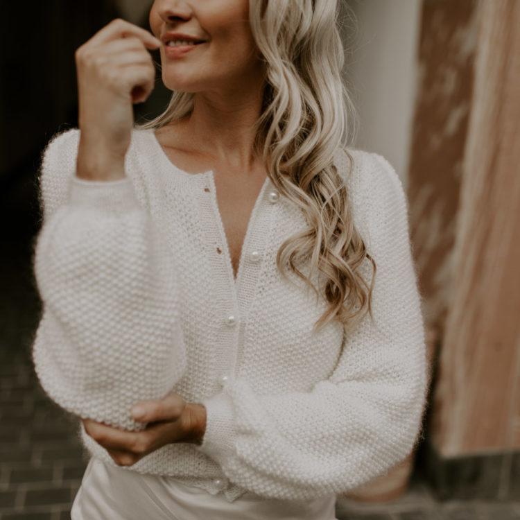 Brautmodell in weißem Kleid und Pullover