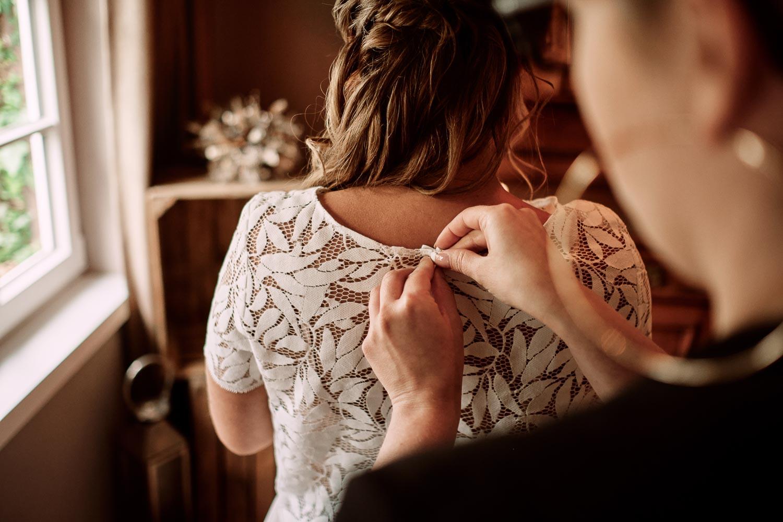 Die Braut wird beim Getting Ready angezogen. Sie trägt ein Brautjäckchen aus Blätterspitze.