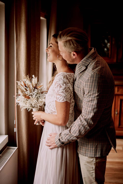 Brautpaar steht am Fenster. Sie trägt ihren Brautstrauß.