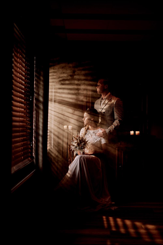 Brautpaar am Fenster. Die Sonne scheint durch die Rolläden.