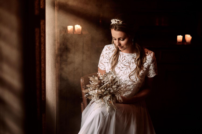 Die Braut mit Brautstrauß in der Hand trägt ein Brautjäckchen aus Blätterspitze und einen Tüllrock.