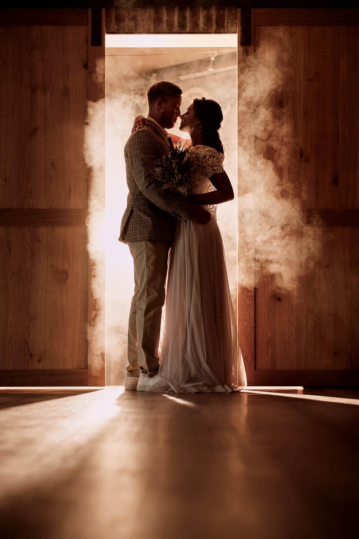 Brautpaar steht in schummrigem Licht vor einer Tür.