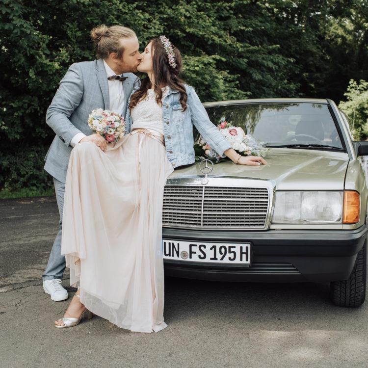 Brautpaar auf grünem Oldtimer Mercedes. Brautkleid in Blush und Bräutigam im blauen Anzug.