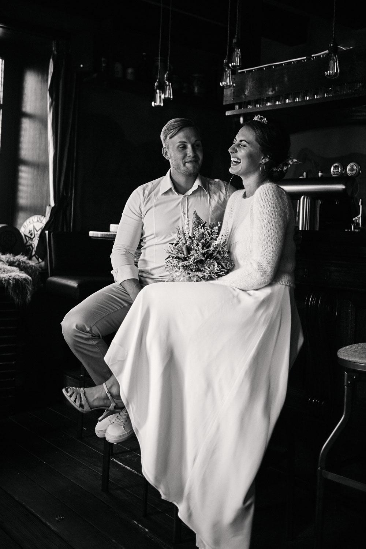 Brautpaar sitzt lachend an der Bar.