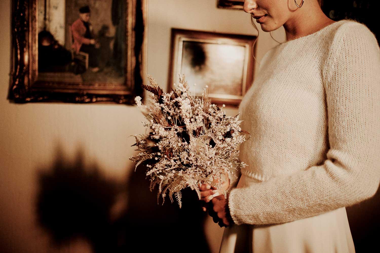 Braut mit Brautpullover, Brautstrauß und Haarschmuck