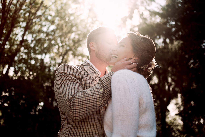 Brautpaar in der Sonne. Der Bräutigam küsst die lachende Braut.
