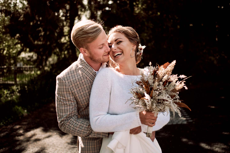 Bräutigam umarmt Braut von hinten. Sie trägt ihren Brautstrauß.