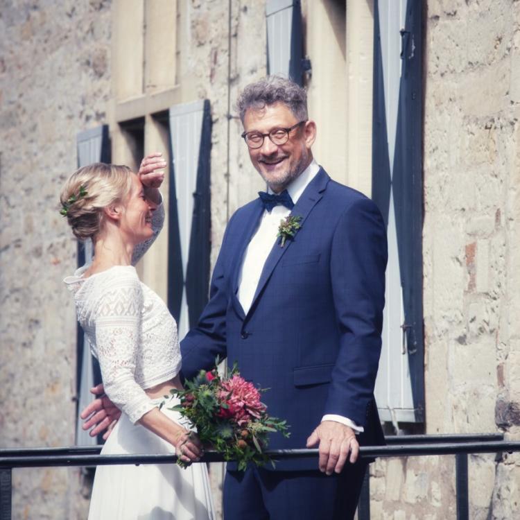Brautpaar vor Steinmauer. Die Braut trägt ein Boho Brautkleid mit Spitzentop und Brautrock aus Chiffon. In der Hand hält sie ihren Brautstrauß in rot pink Tönen. Der Bräutigam trägt einen blauen Anzug mit weißem Hemd.