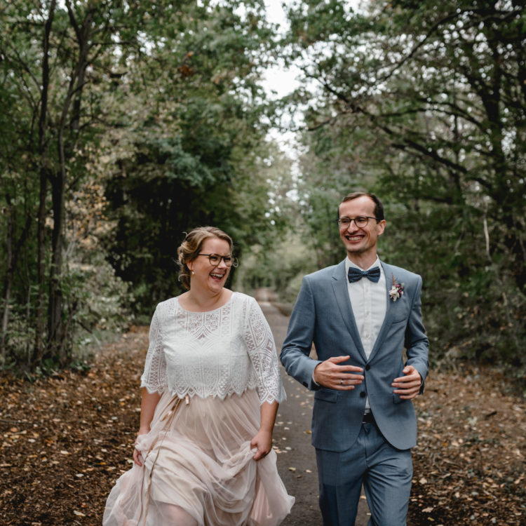 Brautpaar im Wald. Braut trägt zweiteiliges Brautkleid aus Tüllrock in Blush und Brauttop aus geometrischer Spitze. Dazu ein Brautgürtel in roségold. Bräutigam trägt blaugrauen Anzug mit weißem Hemd und Fliege.