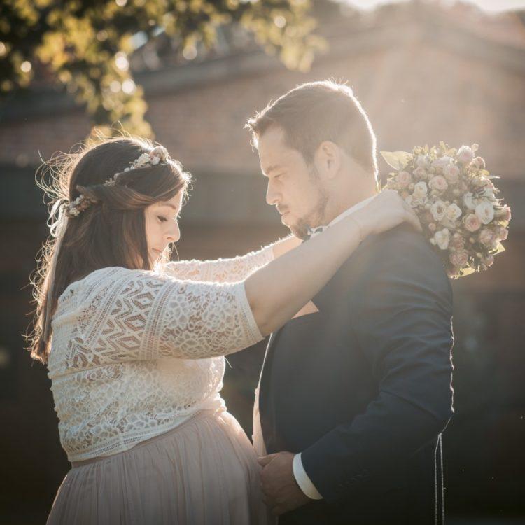 Glückliches Brautpaar. Schwangere Braut mit kurzem Brautrock in Blush Rosa und Top aus Bohospitze. Dazu trägt sie einen Blumenkranz und ihren Brautstrauß. Bräutigam im dunklen Anzug mit weißem Hemd.