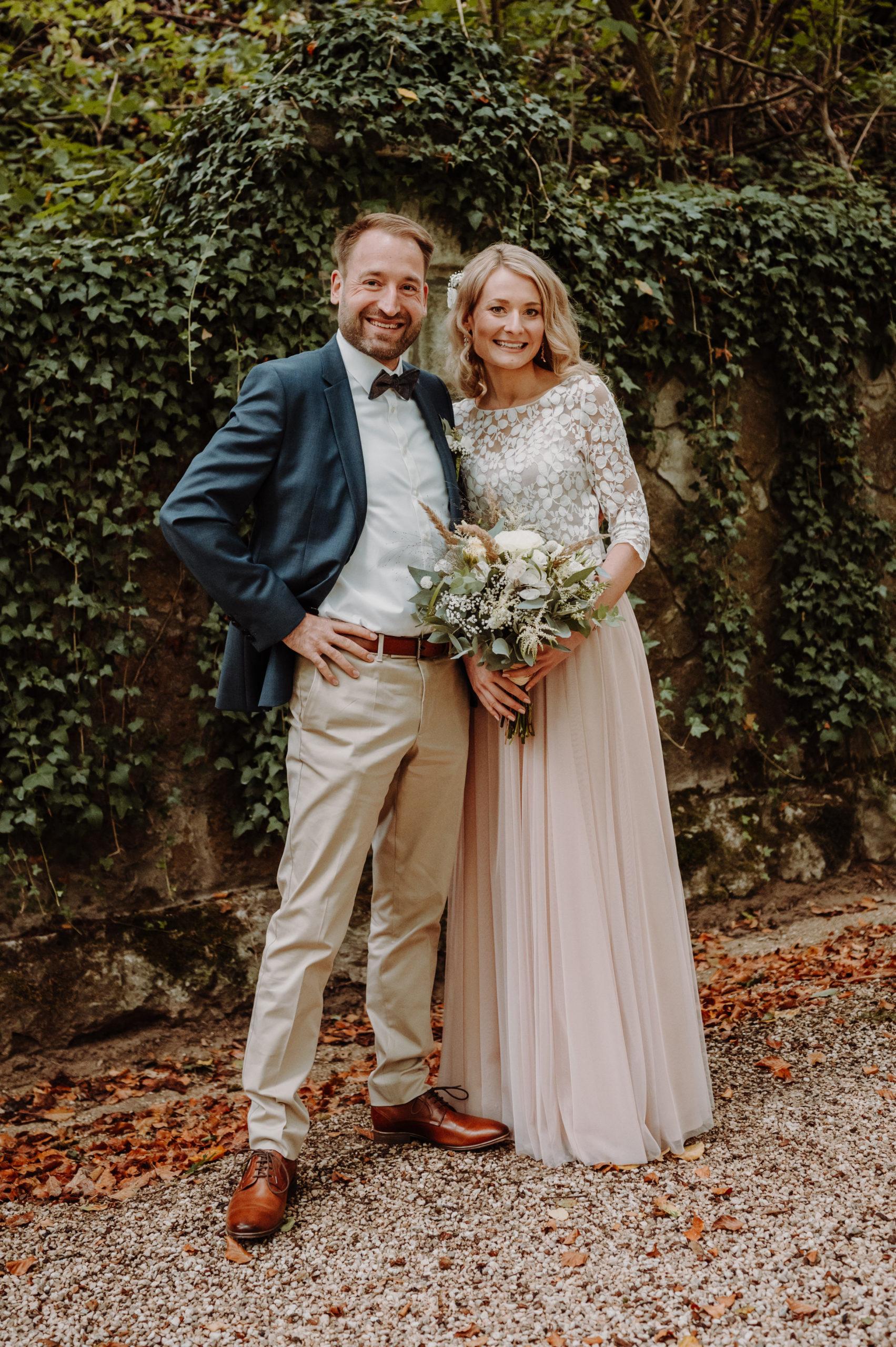 Brautpaar vor mit Wein bewachsener Mauer im Herbst. Braut mit Zweiteiligem Brautkleid aus Tüllrock in Blush und Spitzentop, sie trägt ihren Brautstrauß. Bräutigam mit beiger Hose, weißem Hemd und blauem Sakko.