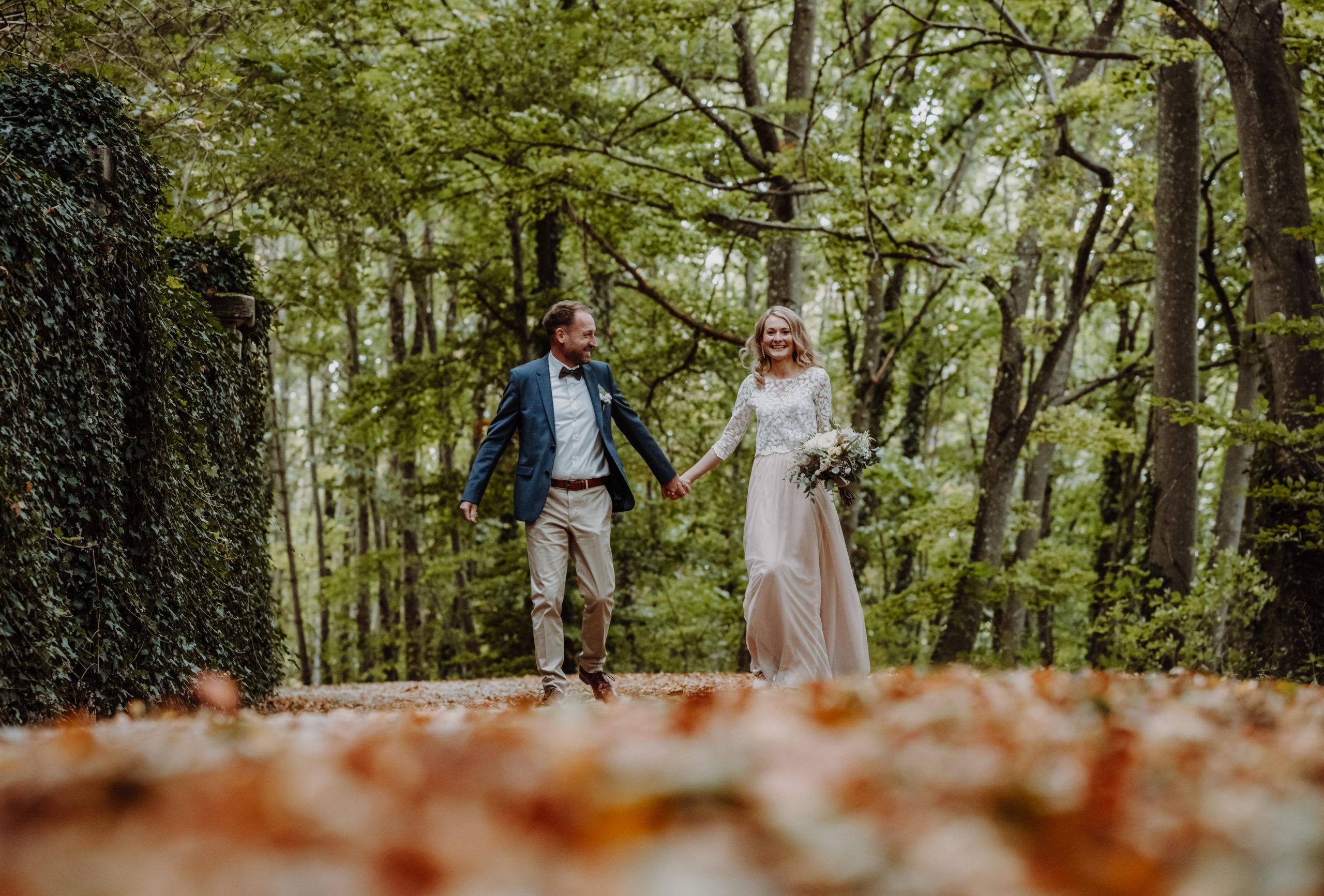 Brautpaar im herbstlichen Wald. Braut mit Zweiteiligem Brautkleid aus Tüllrock in Blush und Spitzentop, sie trägt ihren Brautstrauß. Bräutigam mit beiger Hose, weißem Hemd und blauem Sakko.