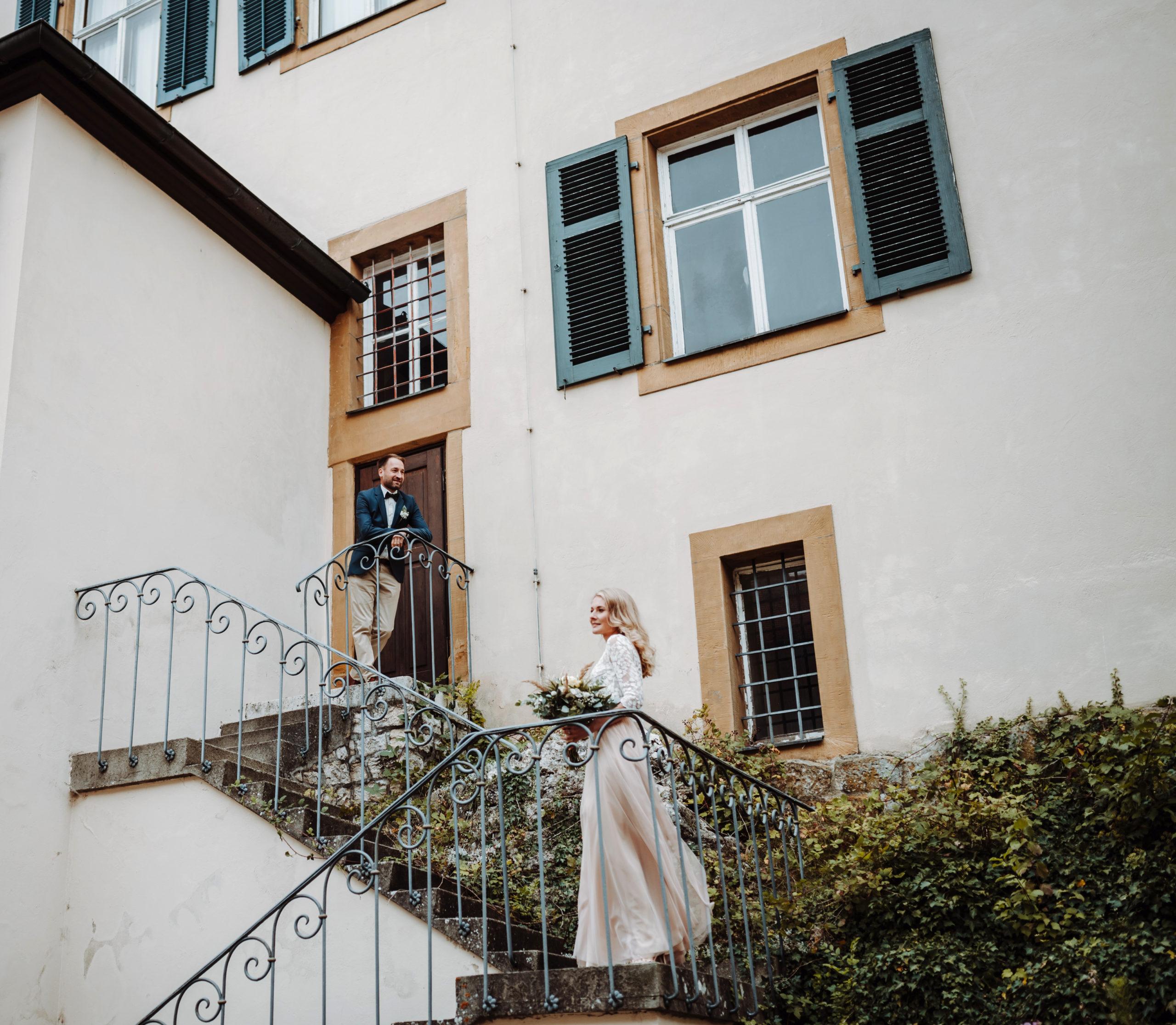 Brautpaar auf Treppe. Braut mit Zweiteiligem Brautkleid aus Tüllrock in Blush und Spitzentop, sie trägt ihren Brautstrauß. Bräutigam mit beiger Hose, weißem Hemd und blauem Sakko.