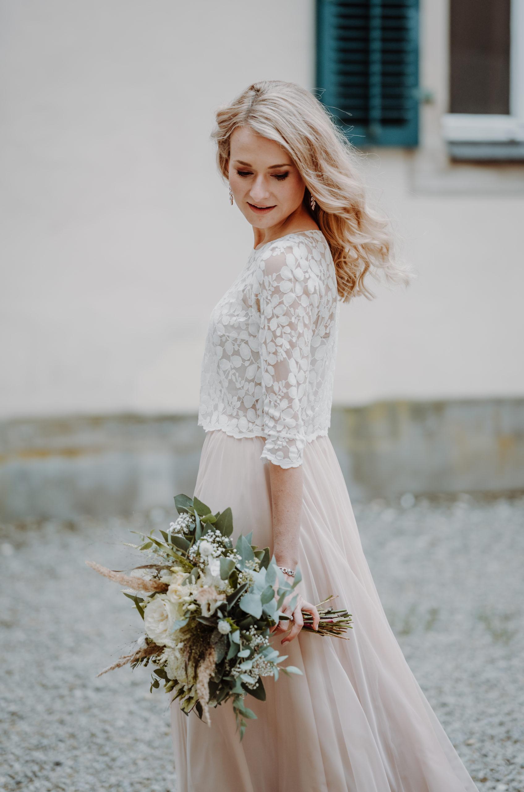 Braut mit Zweiteiligem Brautkleid aus Tüllrock in Blush und Brauttop aus Blätterspitze, sie trägt ihren Brautstrauß.