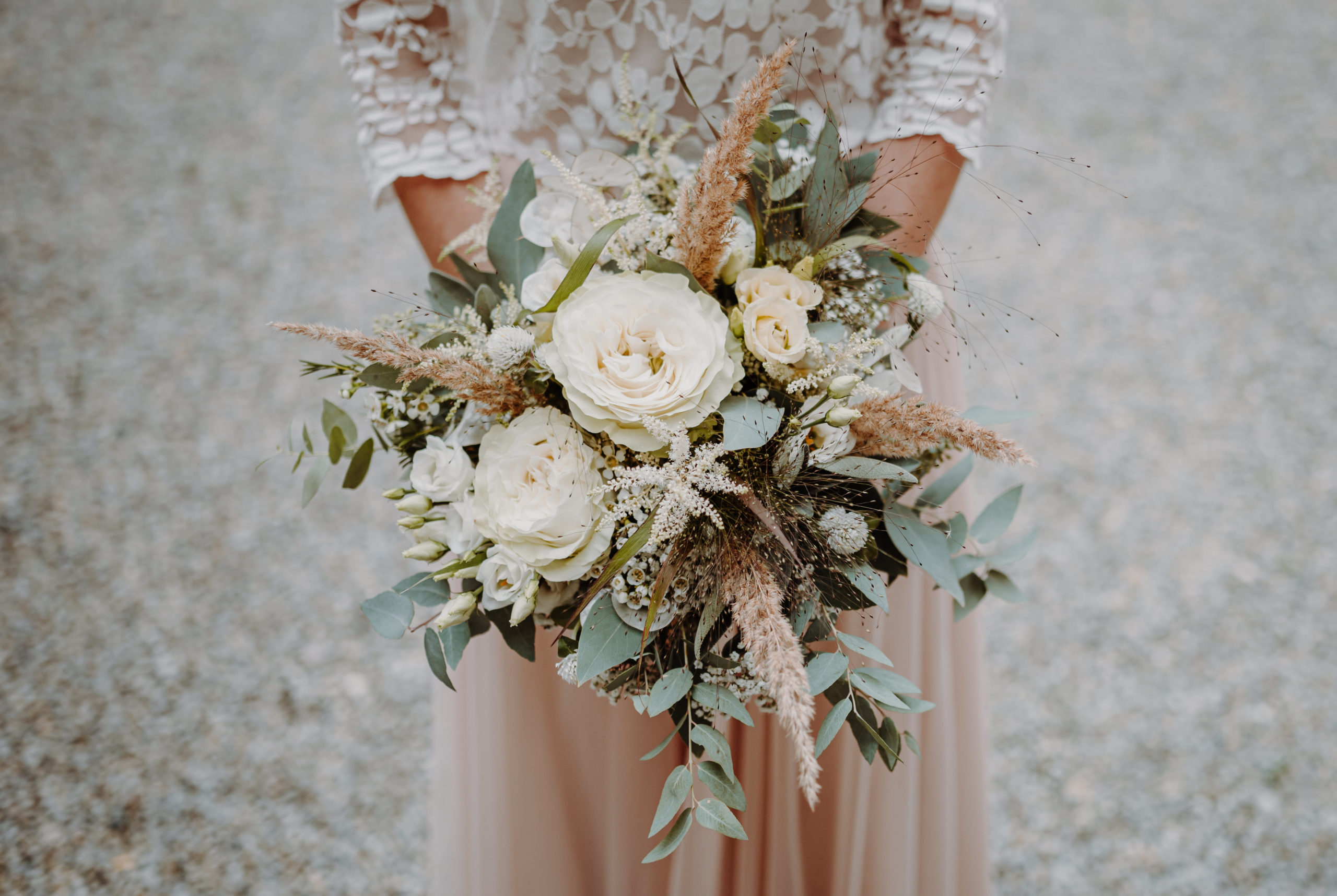 Opulenter Brautstrauß von Braut mit Tüllrock in Blush und Brauttop aus Blätterspitze.