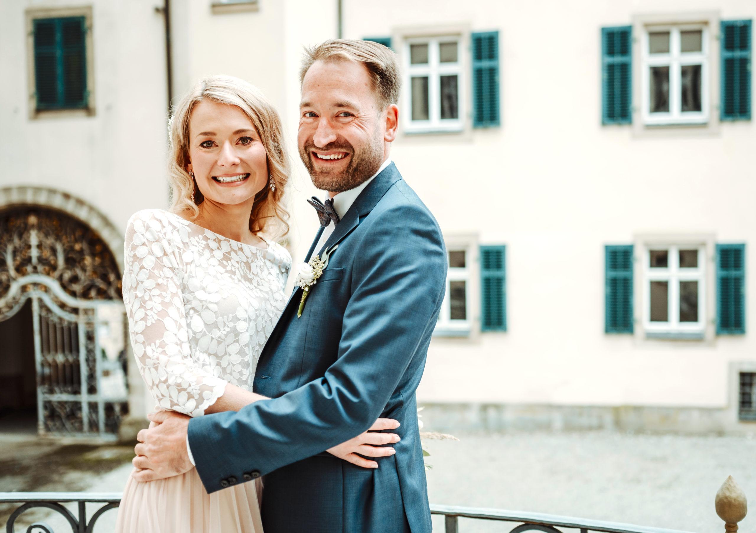 Brautpaar vor Schloss. Braut mit Zweiteiligem Brautkleid aus Tüllrock in Blush und Spitzentop, sie trägt ihren Brautstrauß. Bräutigam mit beiger Hose, weißem Hemd und blauem Sakko.
