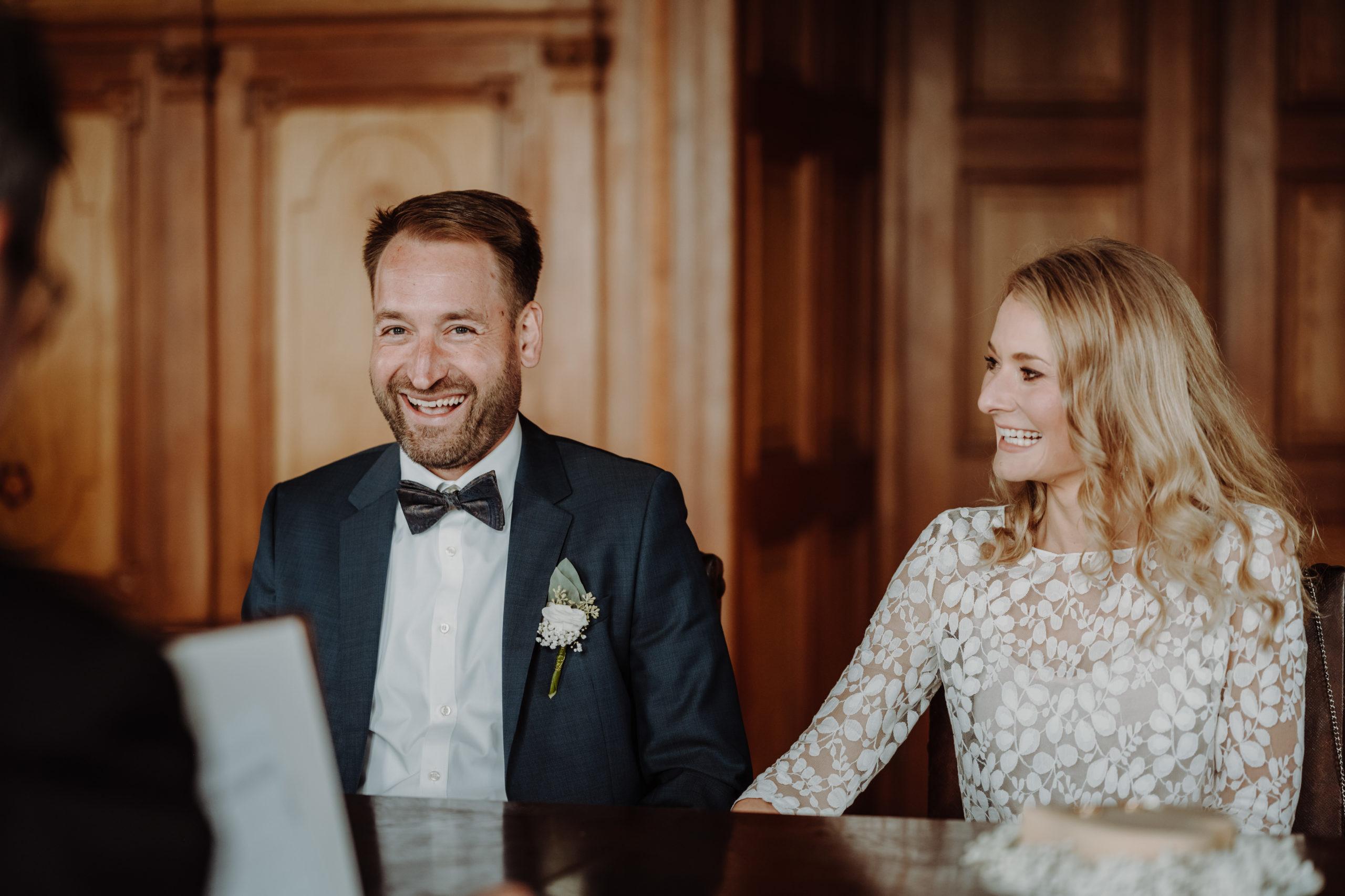 Brautpaar im Standesamt. Sie trägt ein Brauttop mit Blätterspitze und eh ein dunkles Sakko, weißes Hemd und eine Fliege.