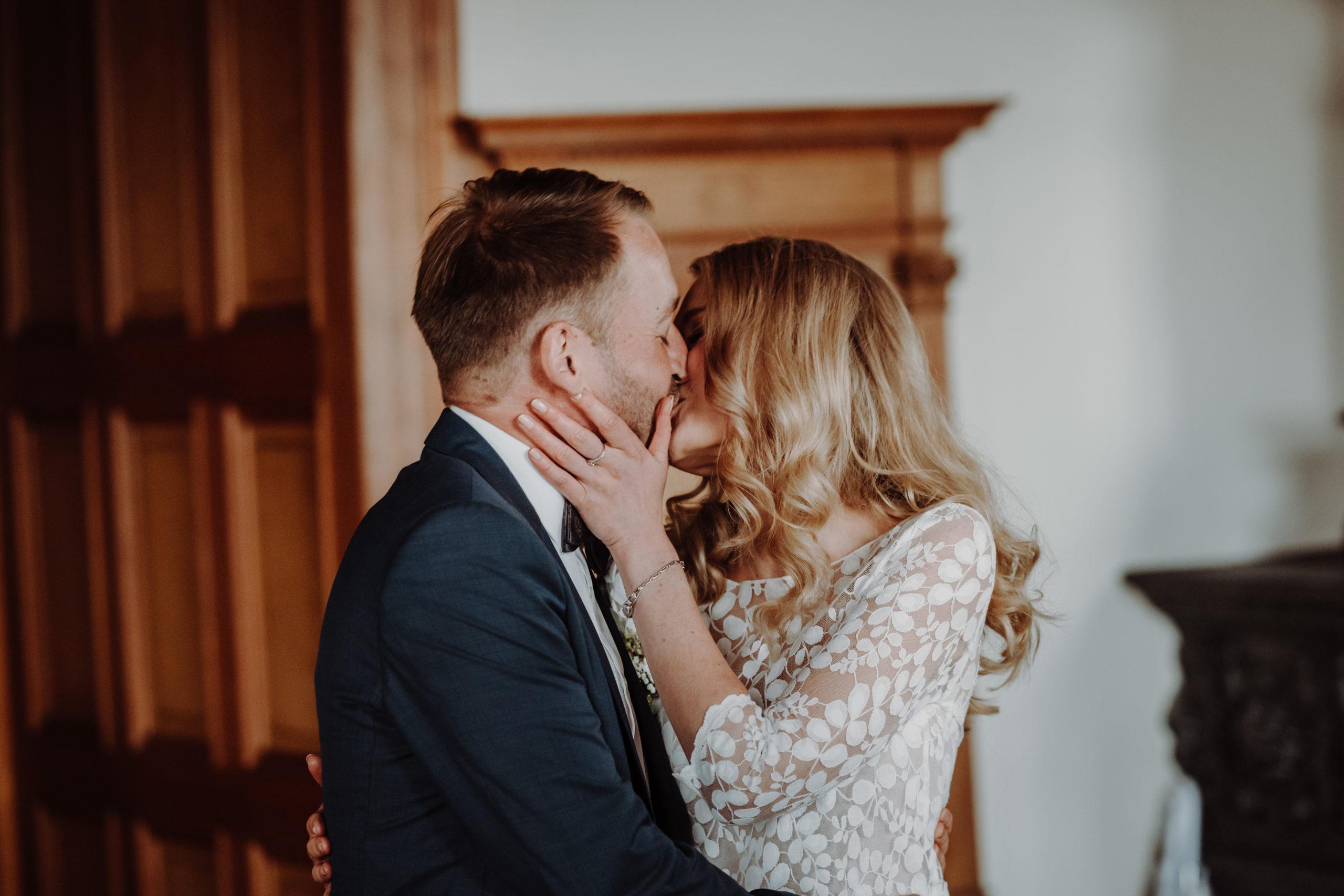 Brautpaar küsst sich im Standesamt. Sie trägt ein Brauttop mit Blätterspitze und eh ein dunkles Sakko, weißes Hemd und eine Fliege.