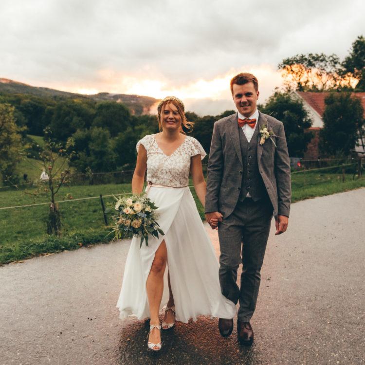 Brautpaar auf Straße an Wiese im Sonnenuntergang. Die Braut trägt ein zweiteiliges Brautkleid mit bodenlangem Chiffonrock mit Beinschlitz, ein Top aus Botanikspitze mit Flügelärmeln, dazu einen Brautgürtel in roségold und einen Blumenkranz im Haar. Außerdem trägt sie ihren Brautstrauß. Der Bräutigam trägt einen grau-braunen Anzug mit roter Fliege.