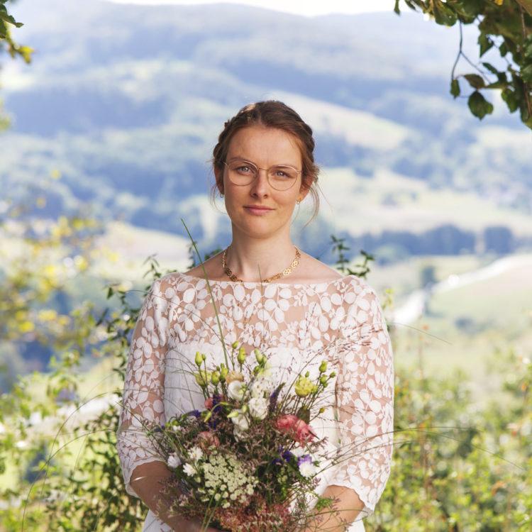 Braut trägt Brauttop aus Spitze und Brautstrauß.