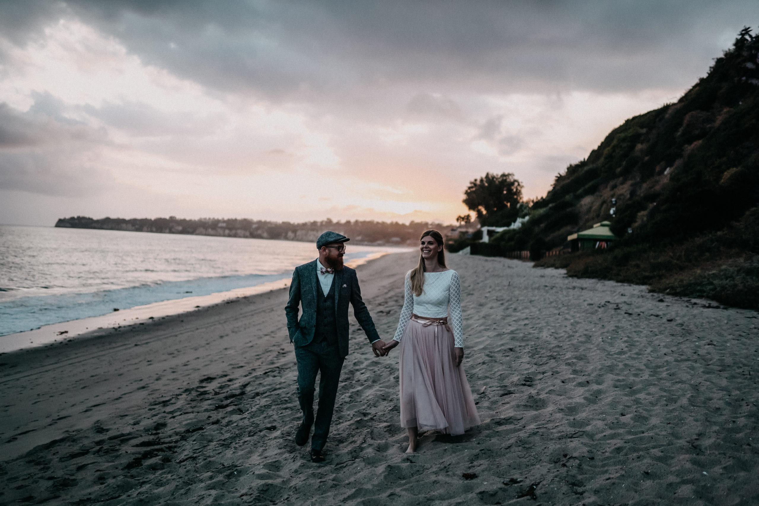 Brautpaar händchenhaltend am Strand bei Sonnenuntergang, lachend. Braut mit zweiteiiligem Kleid mit Midi-Tüllrock in Rosa und langärmeligem Body in Ivory mit geometrischem Muster, Bräutigam im Boho Anzug