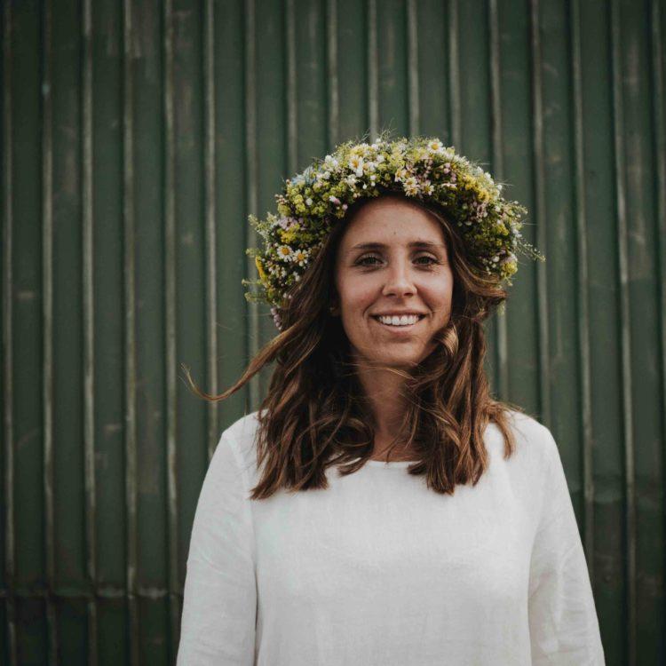 Braut mit Blumenkranz und weißem Leinen Smock Brautkleid vor grünem Tor