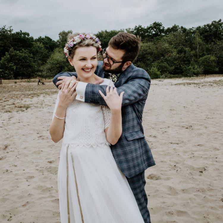 Brautpaar am Strand. Boho Brautkleid mit Brauttop aus geometrischer Spitze und Brautrock aus Softtüll. Dazu Boho Blumenkranz im kurzen Haar. Bräutigam mit blau kartiertem Anzug.