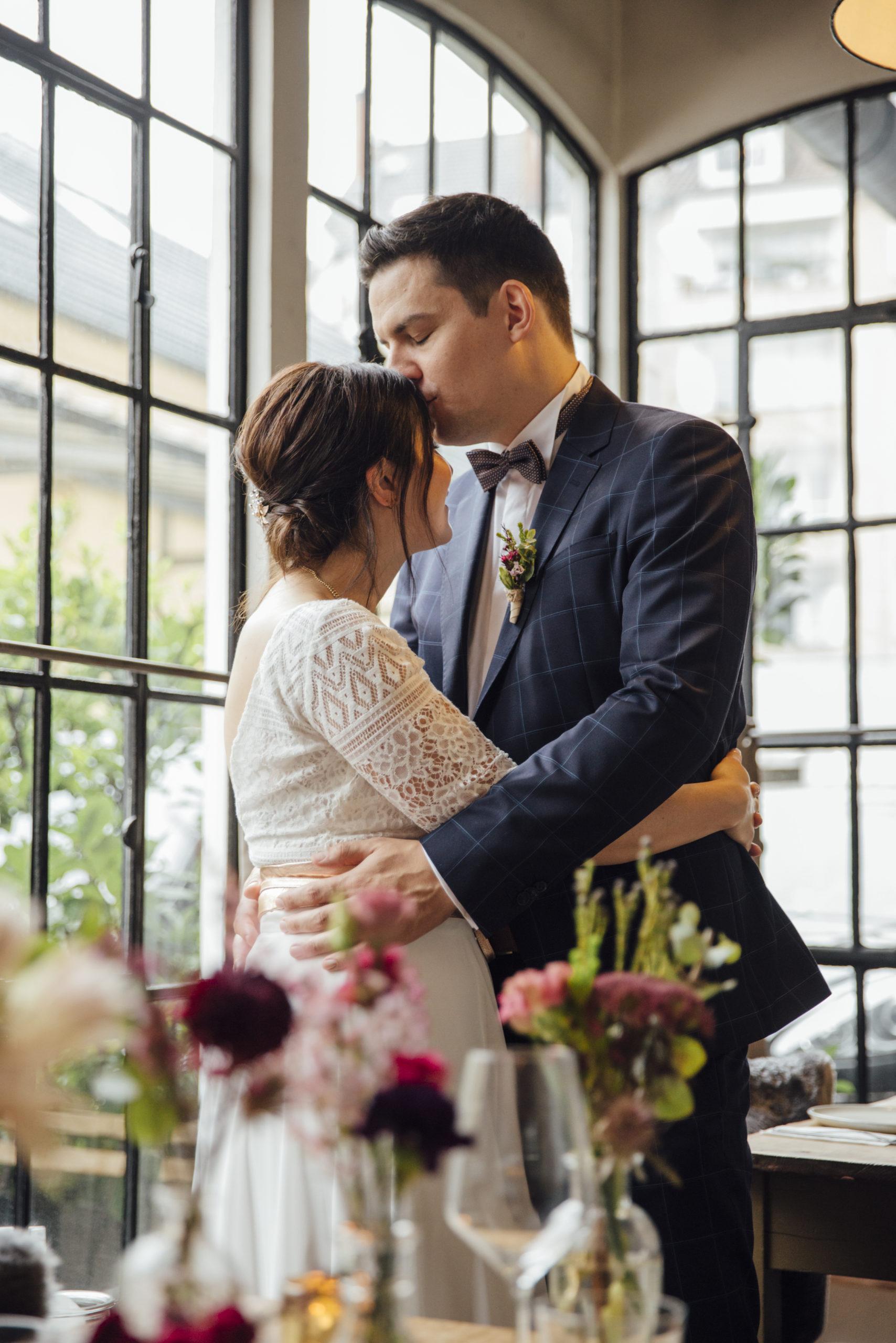 Brautpaar sich umarmend, Braut in weißem Brautkleid-Zweiteiler und Gürtel in Roségold-Metallic, Bräutigam mit blau-kariertem Anzug und Fliege
