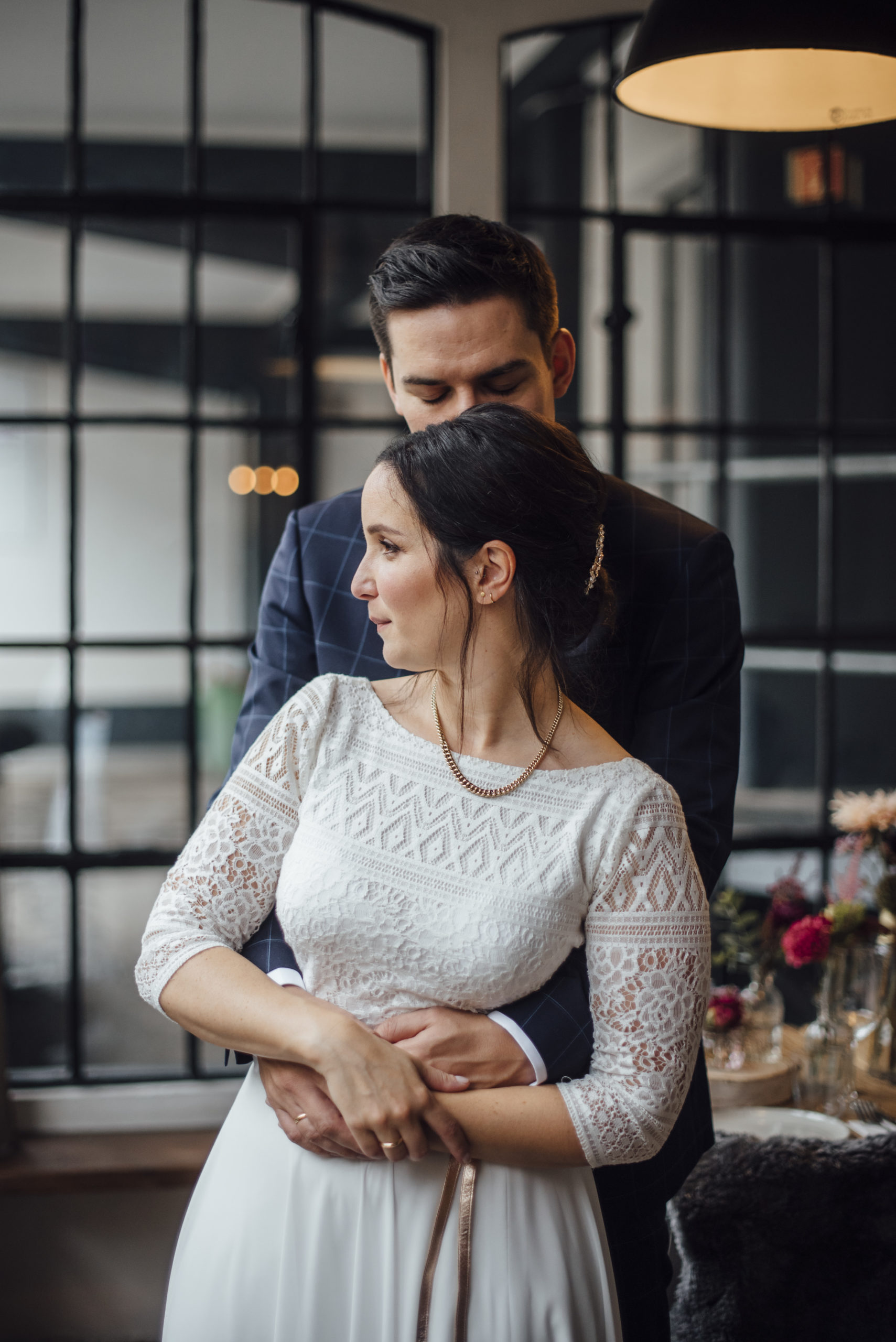 Brautpaar in Hochzeitslocation, Braut in weißem Brautkleid-Zweiteiler und Gürtel in Roségold-Metallic, Bräutigam mit blau-kariertem Anzug und Fliege