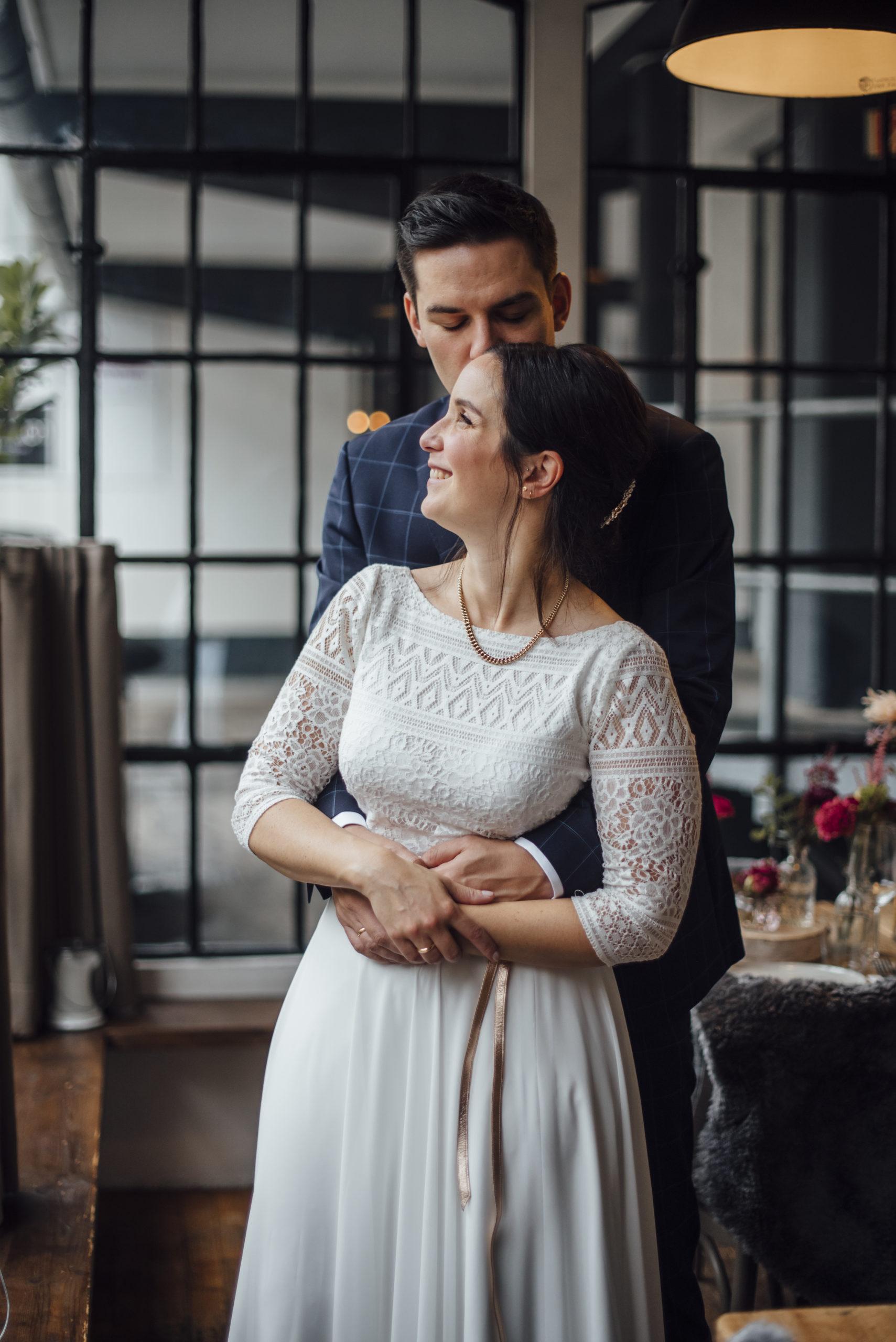Brautpaar lachend, Braut in weißem Brautkleid-Zweiteiler und Gürtel in Roségold-Metallic, Bräutigam mit blau-kariertem Anzug und Fliege