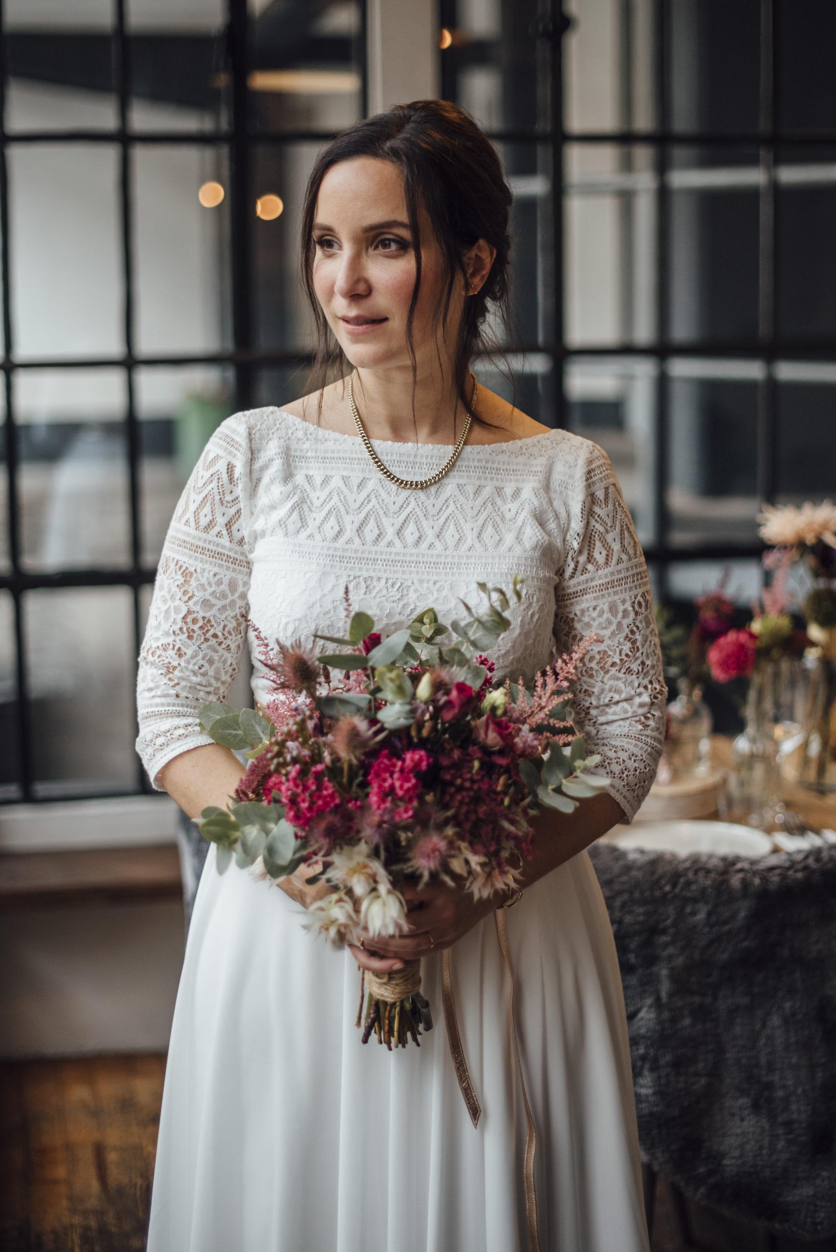 Braut in weißem Brautkleid-Zweiteiler, bunten Blumenstrauss haltend