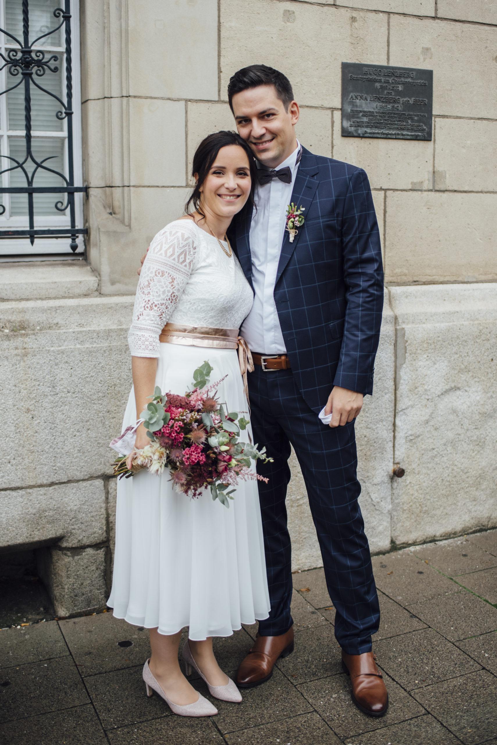 Brautpaar in Kamera lachend, Braut mit buntem Strauss, weißem Brautkleid-Zweiteiler und Gürtel in Roségold-Metallic, Bräutigam mit blau-kariertem Anzug und Fliege