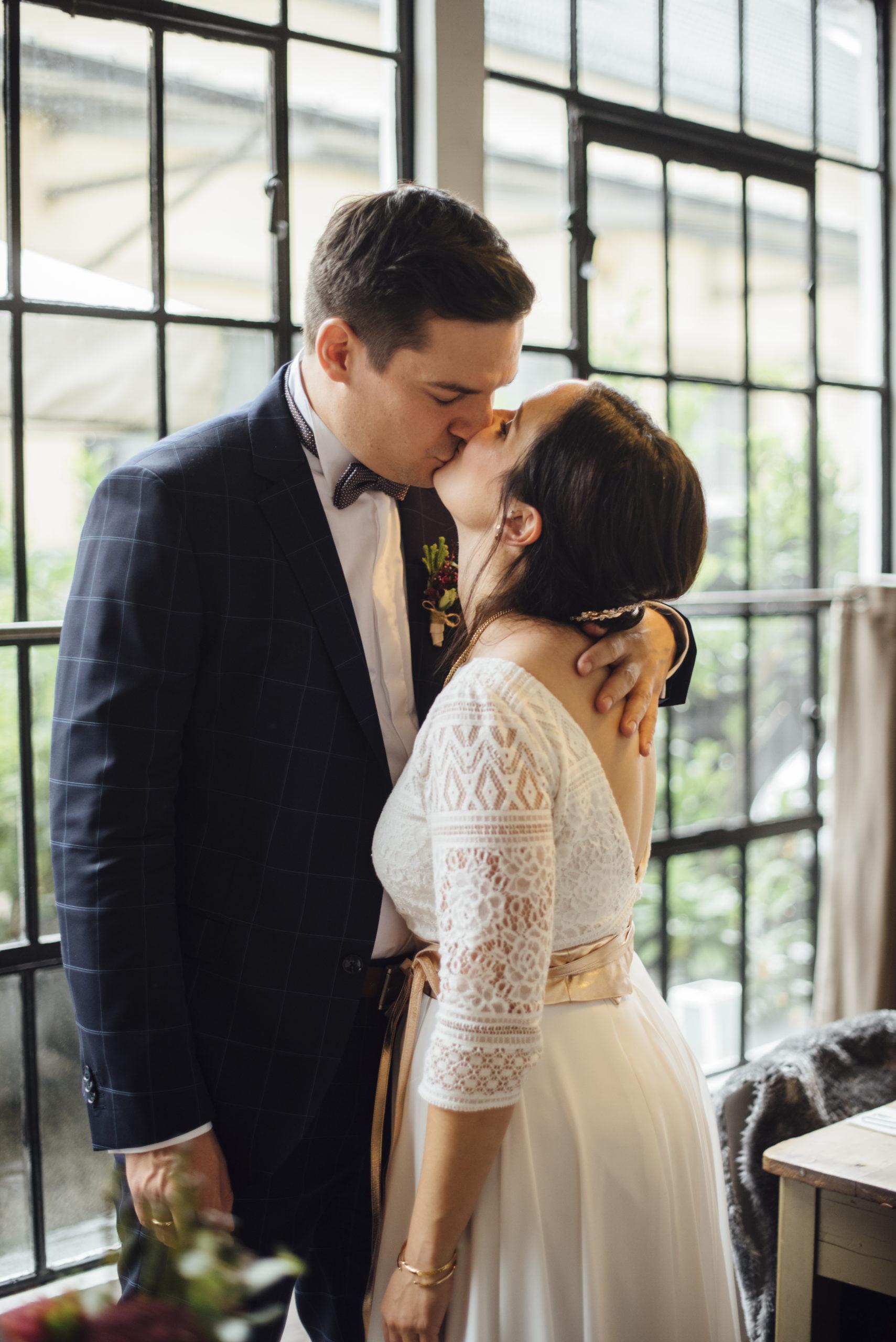 Brautpaar sich küssend, Braut in weißem Brautkleid-Zweiteiler und Gürtel in Roségold-Metallic, Bräutigam mit blau-kariertem Anzug und Fliege