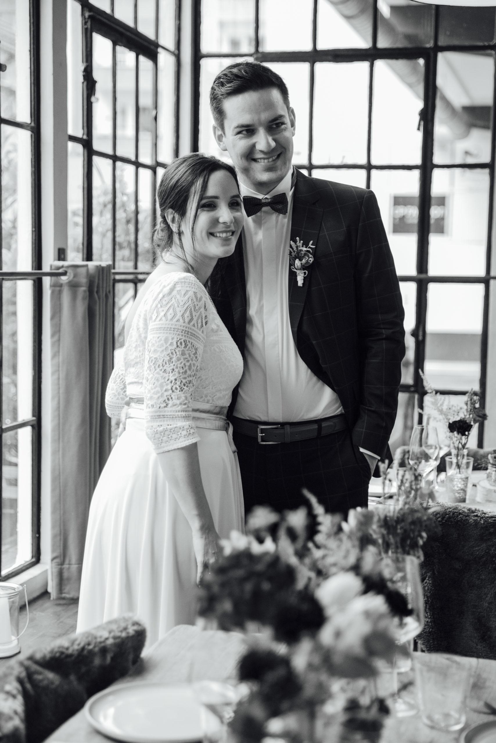 Schwarz-Weiß-Foto: Brautpaar lachend, Braut in weißem Brautkleid-Zweiteiler und Gürtel in Roségold-Metallic, Bräutigam mit blau-kariertem Anzug und Fliege