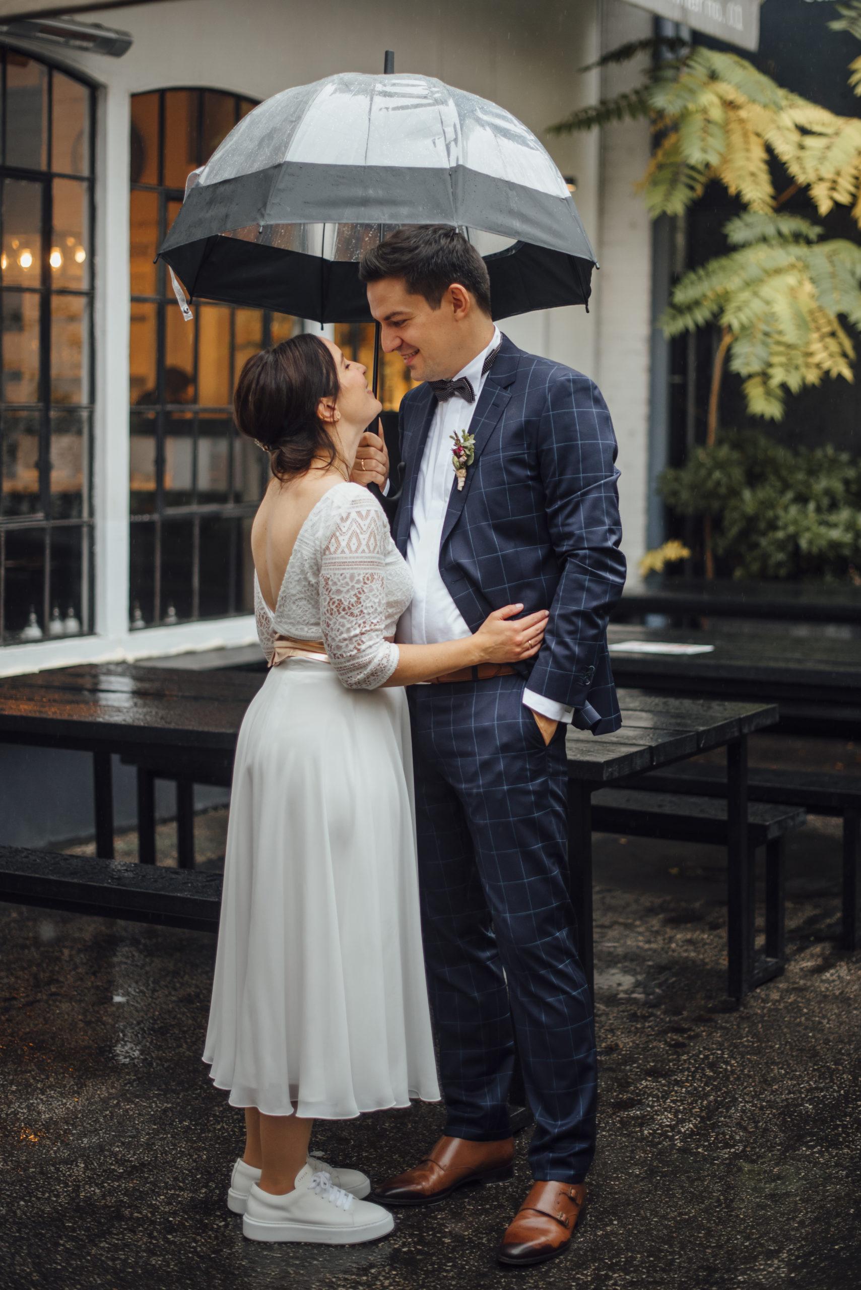 Brautpaar unter transparentem Regenschirm, sich anlächelnd