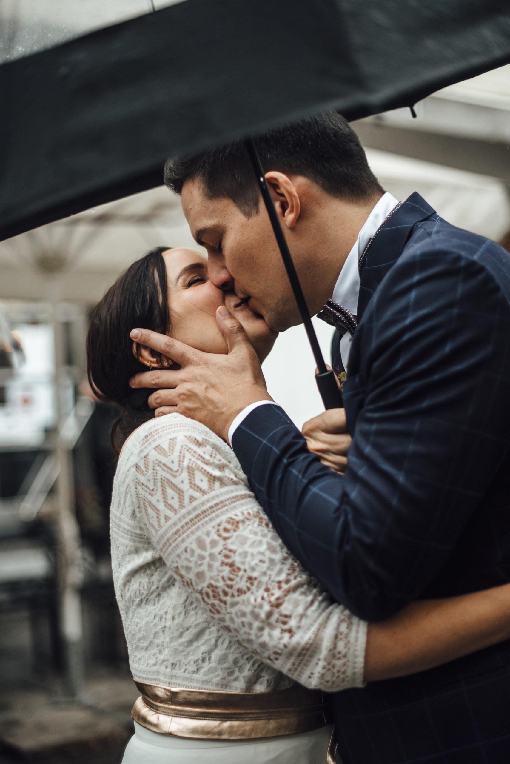 Brautpaar unter Regenschirm, sich küssend