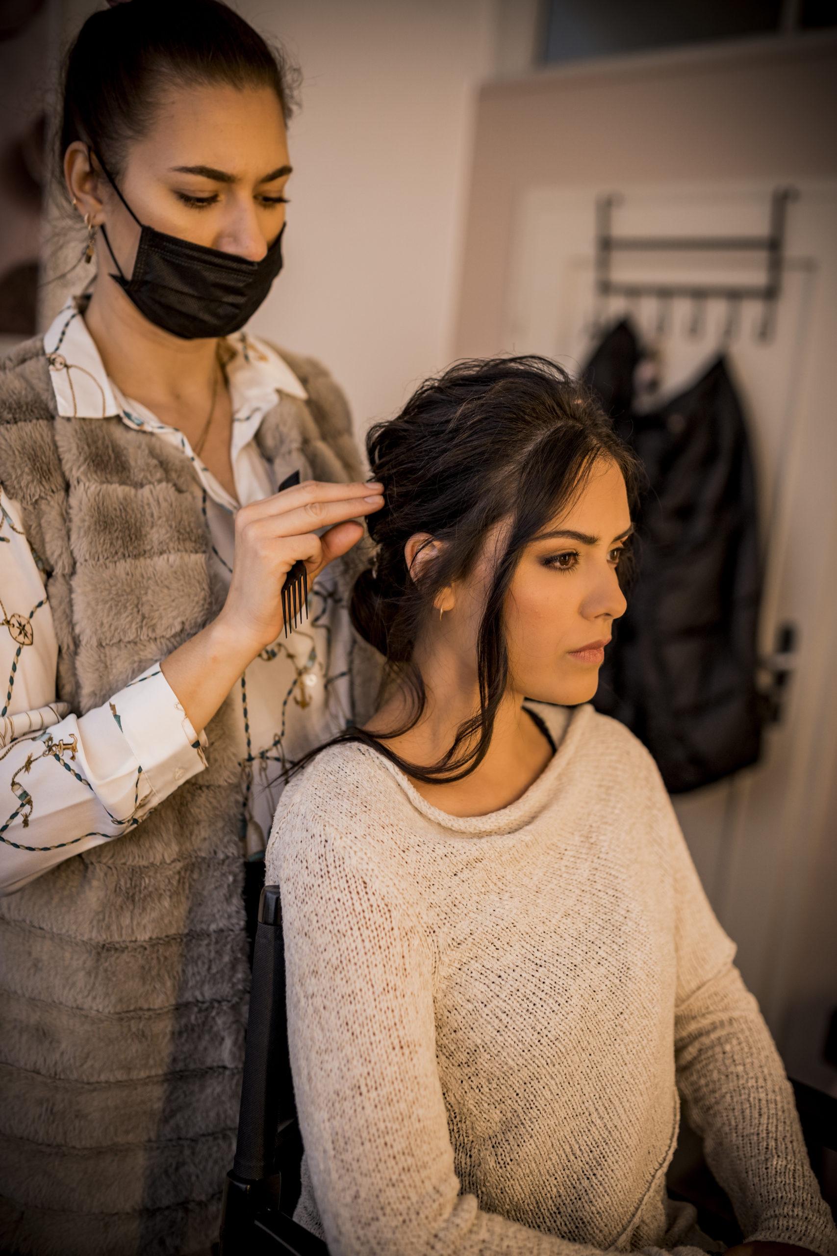 noni Brautmode, Styled Shoot, Getting Ready, Model am Schminktisch, Stylistin mit Mundschutz frisiert Model