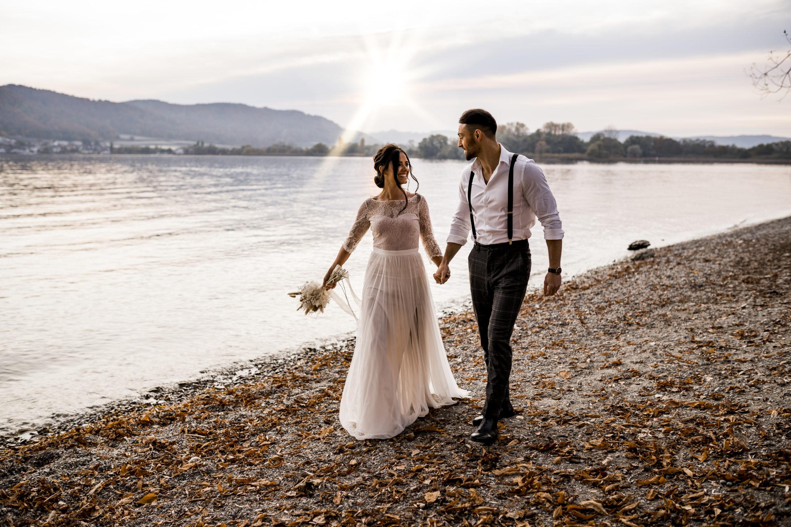 noni Brautmode, Styled Shoot am Bodensee, Model-Pärchen händchenhaltend am Seeufer bei Sonnenschein, Braut mit zweiteiligem Brautkleid in Puderrosa-Optik und Brautstrauss, Bräutigam mit Hemd und Hosenträgern