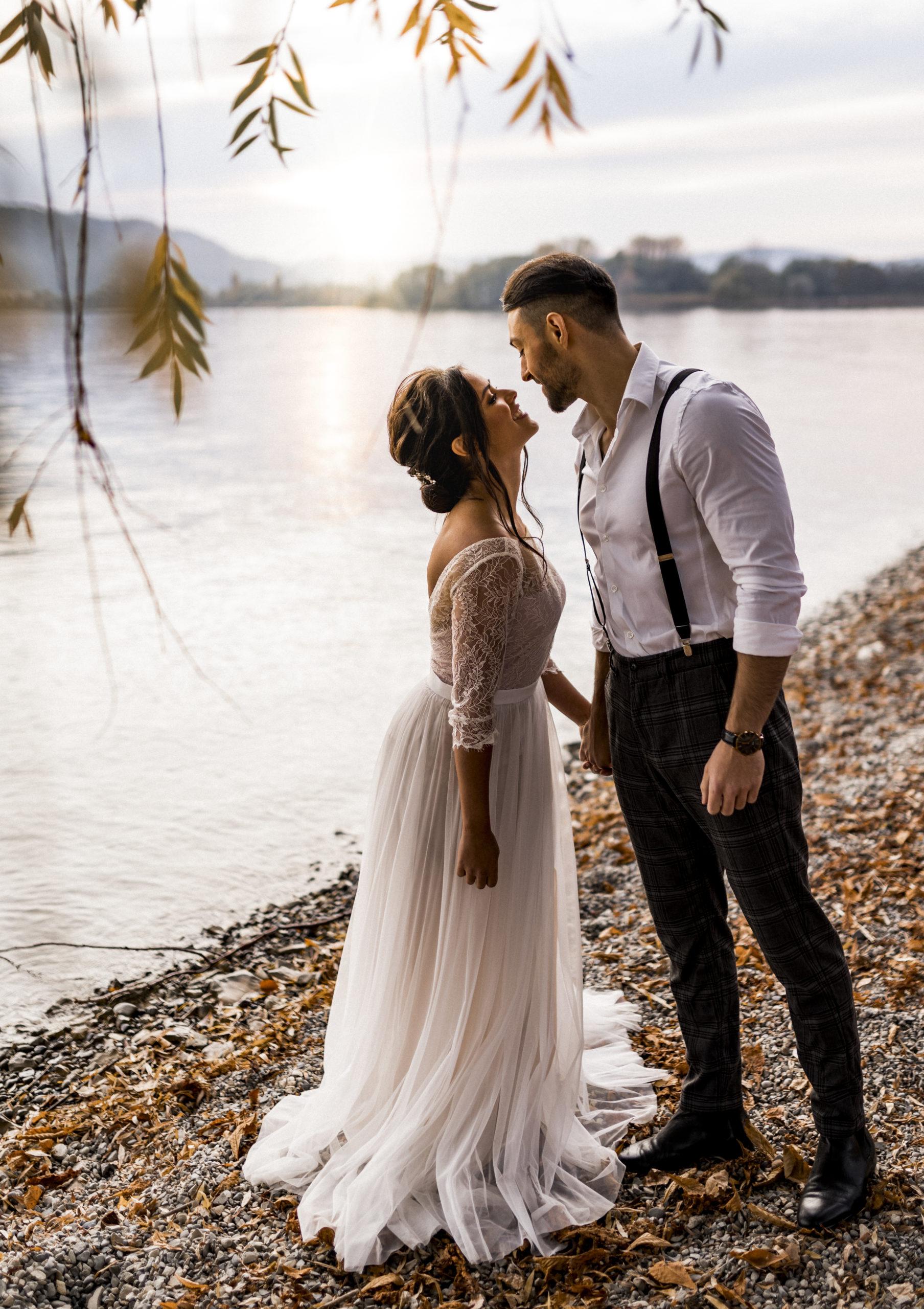 noni Brautmode, Styled Shoot am Bodensee, Model-Pärchen händchenhaltend am Seeufer bei Sonnenschein, Braut mit zweiteiligem Brautkleid in Puderrosa-Optik und Brautstrauss, Bräutigam mit Hemd und Hosenträgern, beide lachend