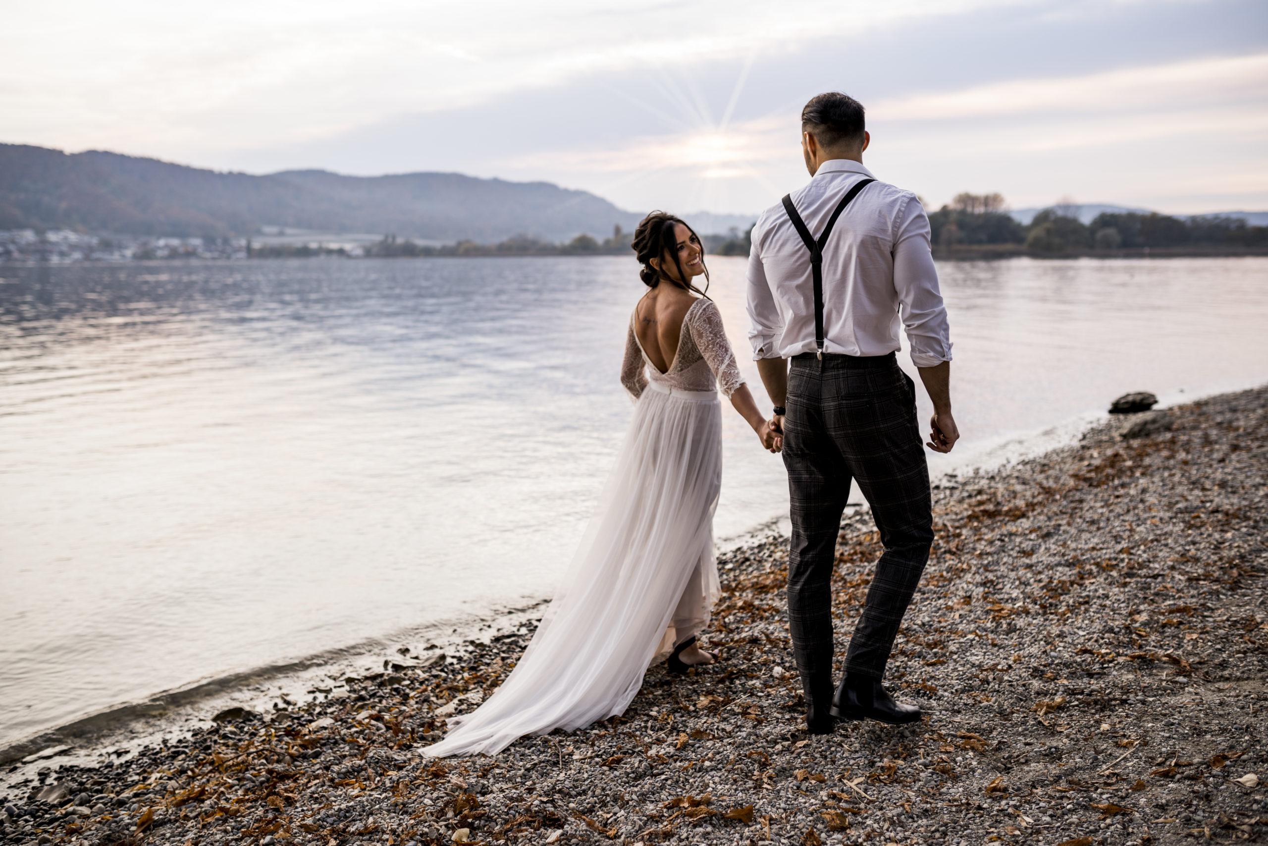 noni Brautmode, Styled Shoot am Bodensee, Model-Pärchen händchenhaltend am Seeufer bei Sonnenschein, Braut mit zweiteiligem Brautkleid in Puderrosa-Optik und Brautstrauss, Bräutigam mit Hemd und Hosenträgern, Rückenansicht