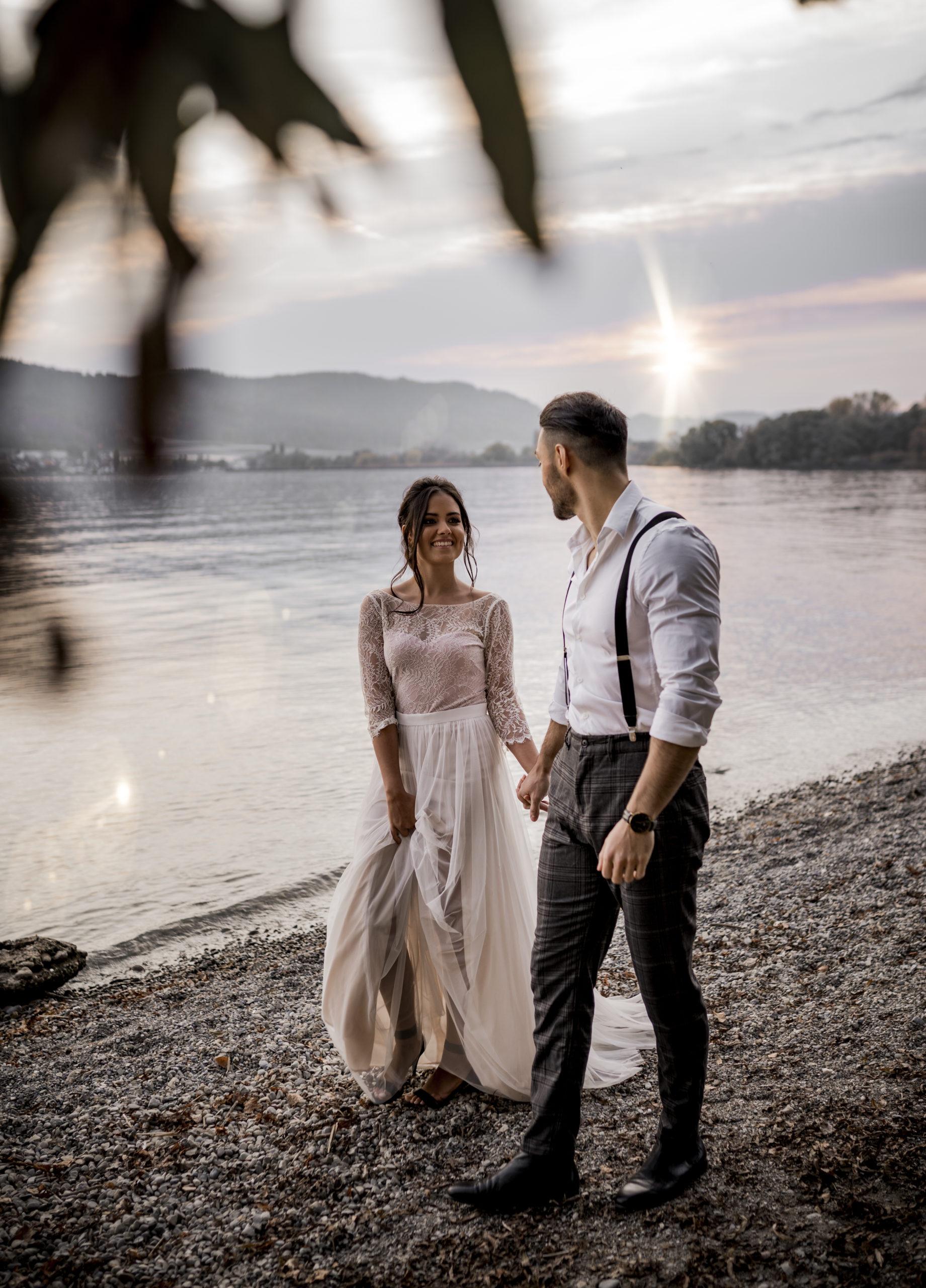 noni Brautmode, Styled Shoot am Bodensee, Model-Pärchen händchenhaltend am Seeufer bei Sonnenschein, Braut mit zweiteiligem Brautkleid in Puderrosa-Optik und Brautstrauss, Bräutigam mit Hemd und Hosenträgern, Vorderansicht, beide lachend