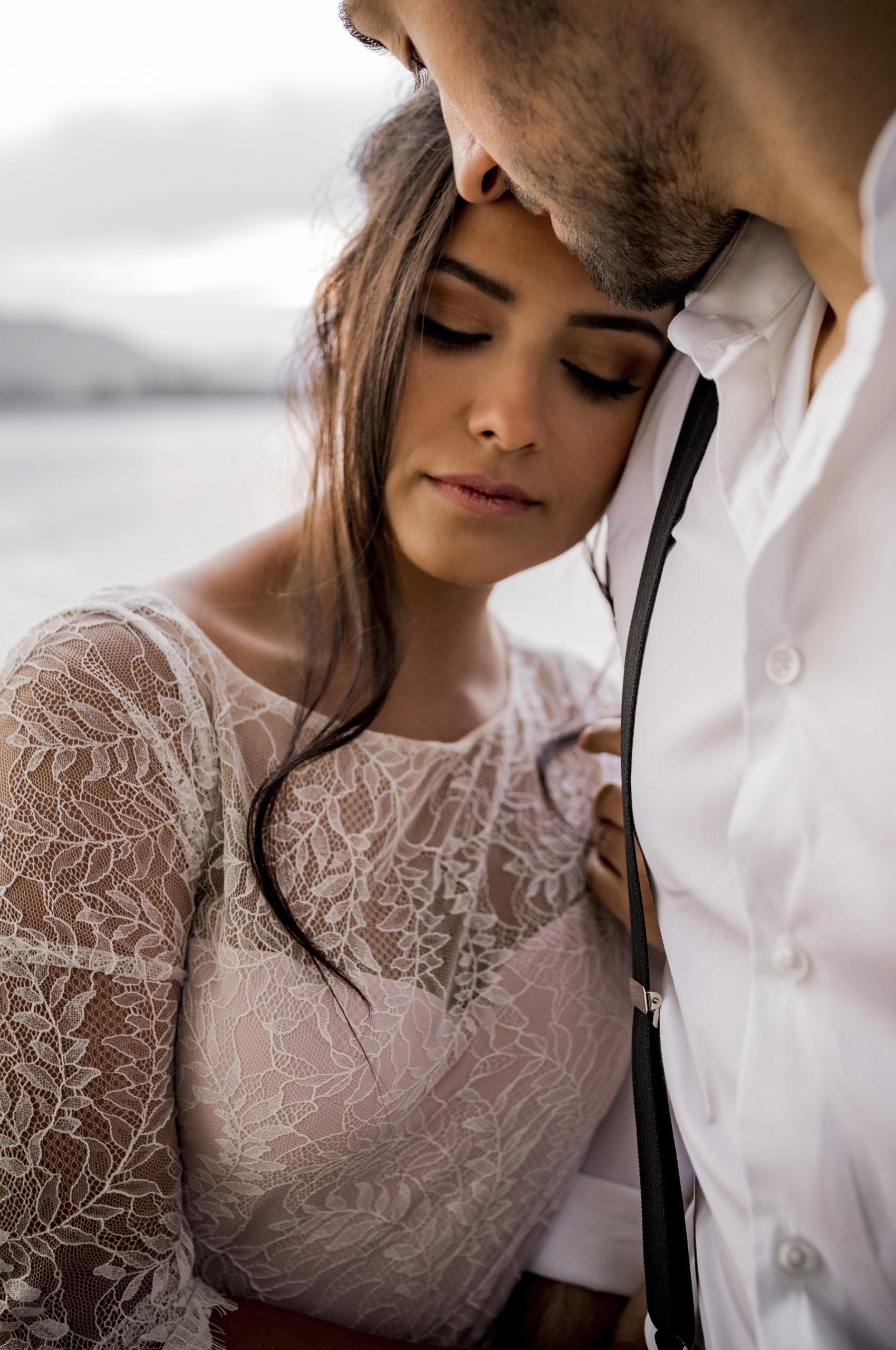 noni Brautmode, Styled Shoot am Bodensee, Model-Pärchen händchenhaltend am Seeufer bei Sonnenschein, Braut mit zweiteiligem Brautkleid in Puderrosa-Optik, Bräutigam mit Hemd und Hosenträgern, umarmend, Nahaufnahme