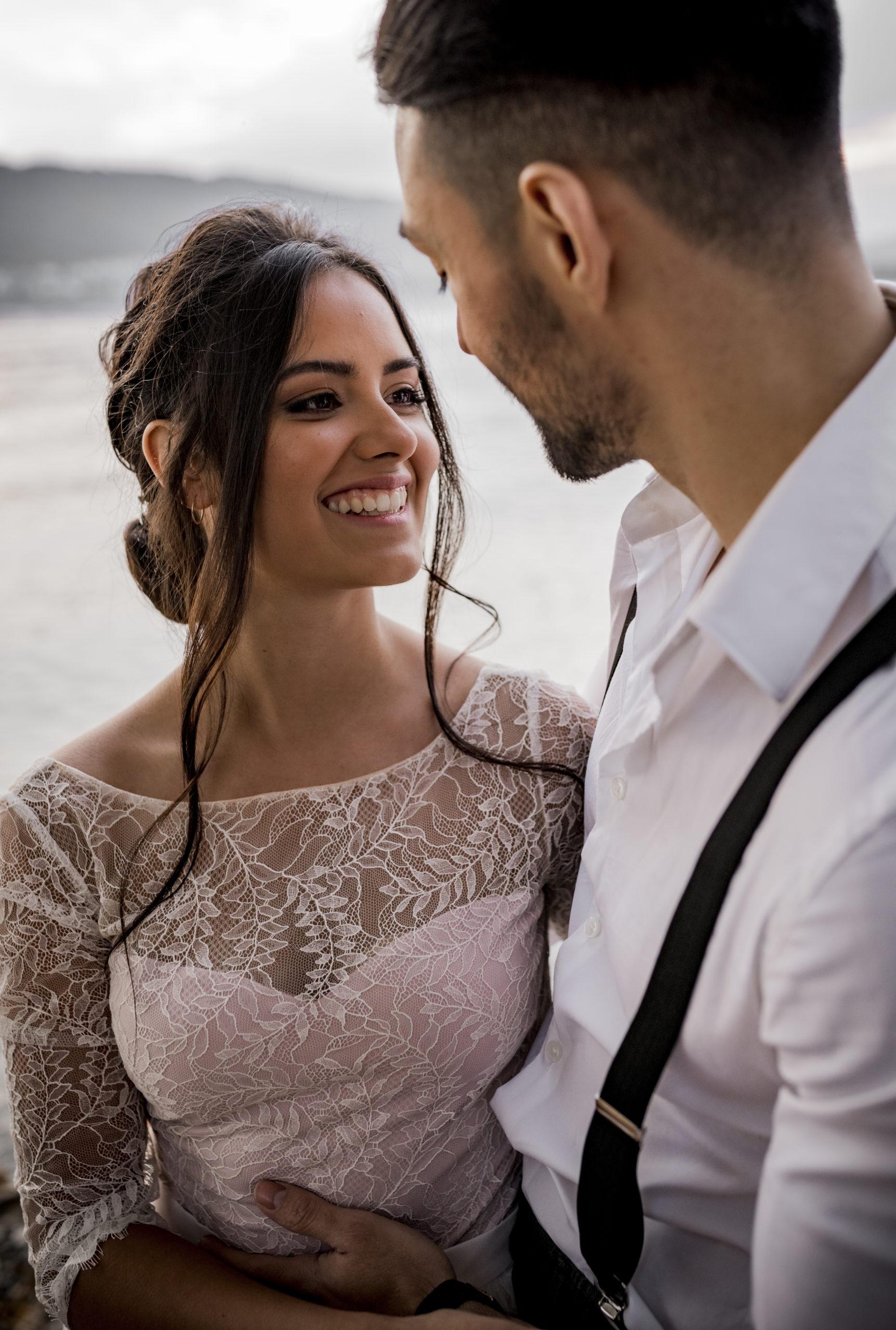noni Brautmode, Styled Shoot am Bodensee, Model-Pärchen händchenhaltend am Seeufer bei Sonnenschein, Braut mit zweiteiligem Brautkleid in Puderrosa-Optik, Bräutigam mit Hemd und Hosenträgern, umarmend, beide lachend, Nahaufnahme