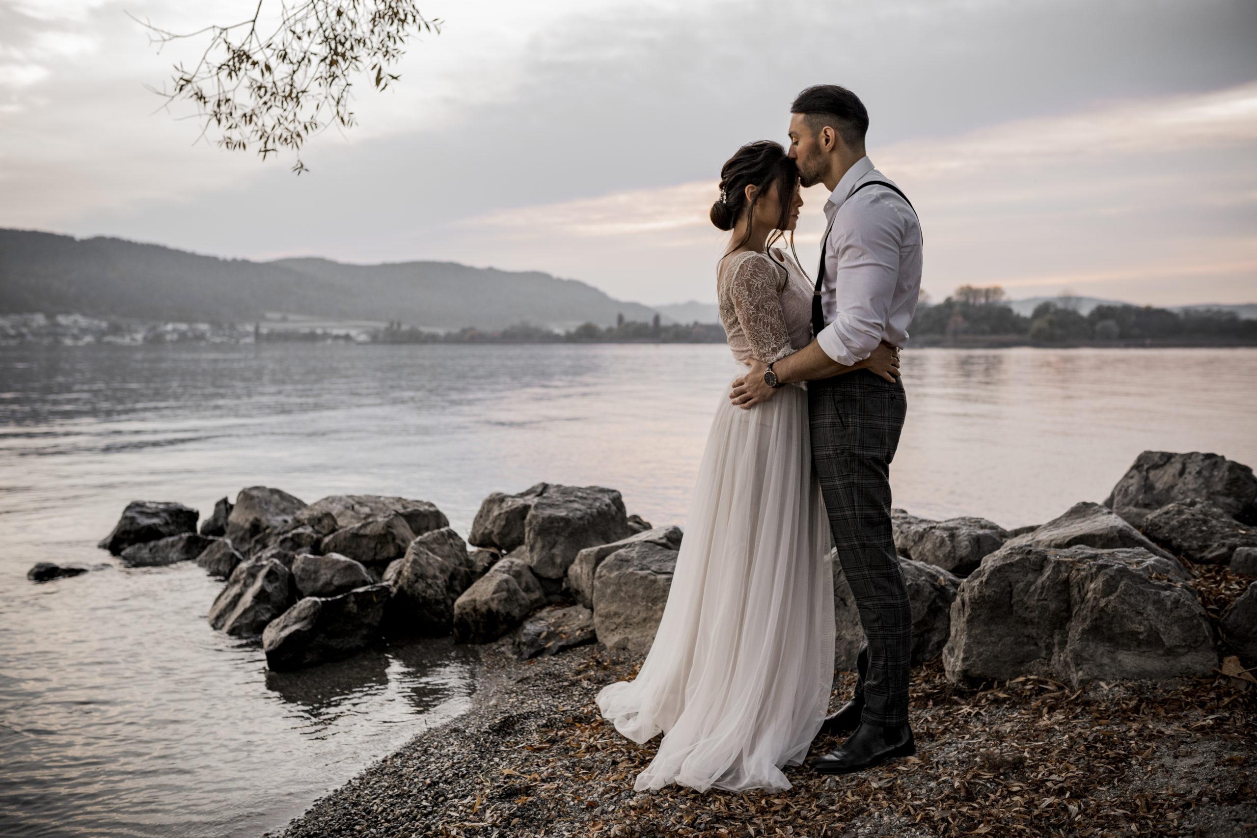 noni Brautmode, Styled Shoot am Bodensee, Model-Pärchen am Seeufer bei Sonnenschein, Braut mit zweiteiligem Brautkleid in Puderrosa-Optik, Bräutigam mit Hemd und Hosenträgern