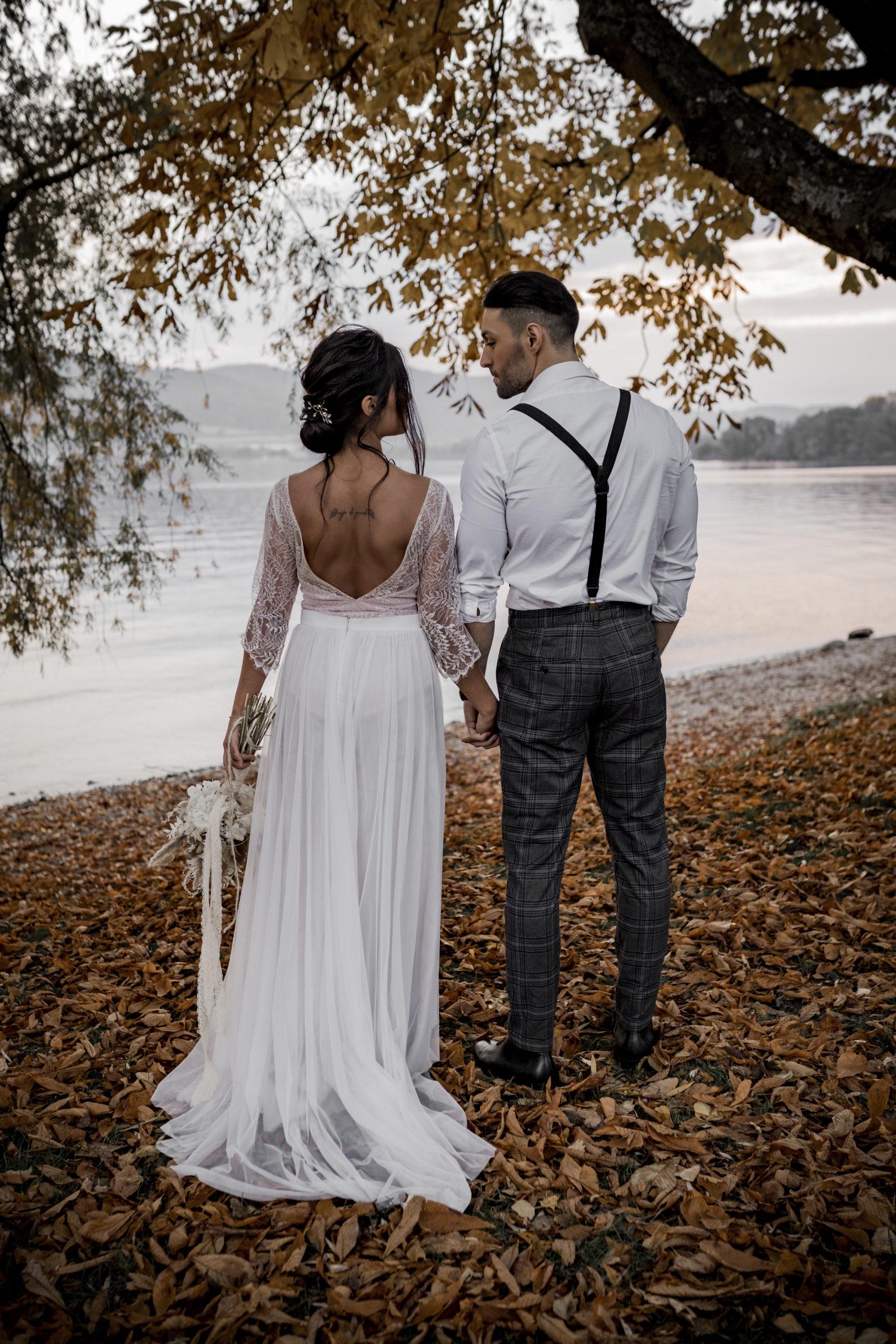 noni Brautmode, Styled Shoot am Bodensee, Model-Pärchen am Seeufer bei Sonnenschein, Braut mit zweiteiligem Brautkleid in Puderrosa-Optik, Bräutigam mit Hemd und Hosenträgern, Rückenansichr: rückenfreies Brautkleid
