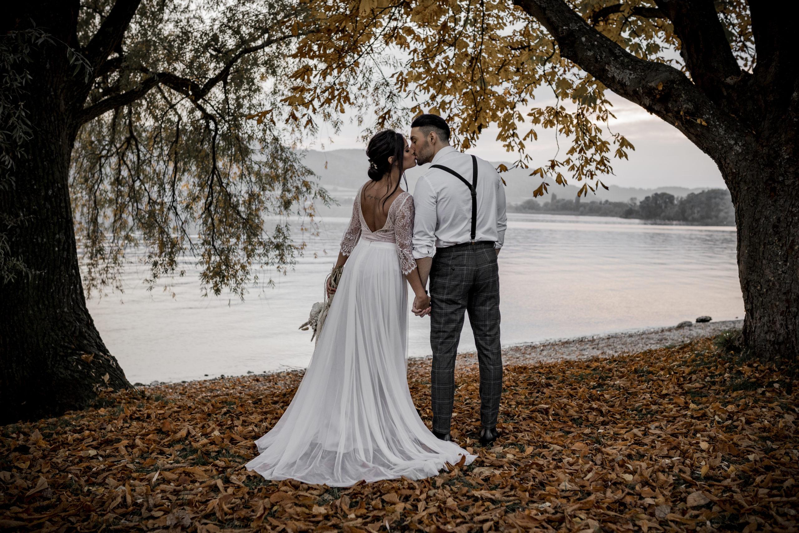noni Brautmode, Styled Shoot am Bodensee, Model-Pärchen am Seeufer bei Sonnenschein, Braut mit zweiteiligem Brautkleid in Puderrosa-Optik, Bräutigam mit Hemd und Hosenträgern, rückenfreies Brautkleid, Rückenansicht, Brautpaar küssend