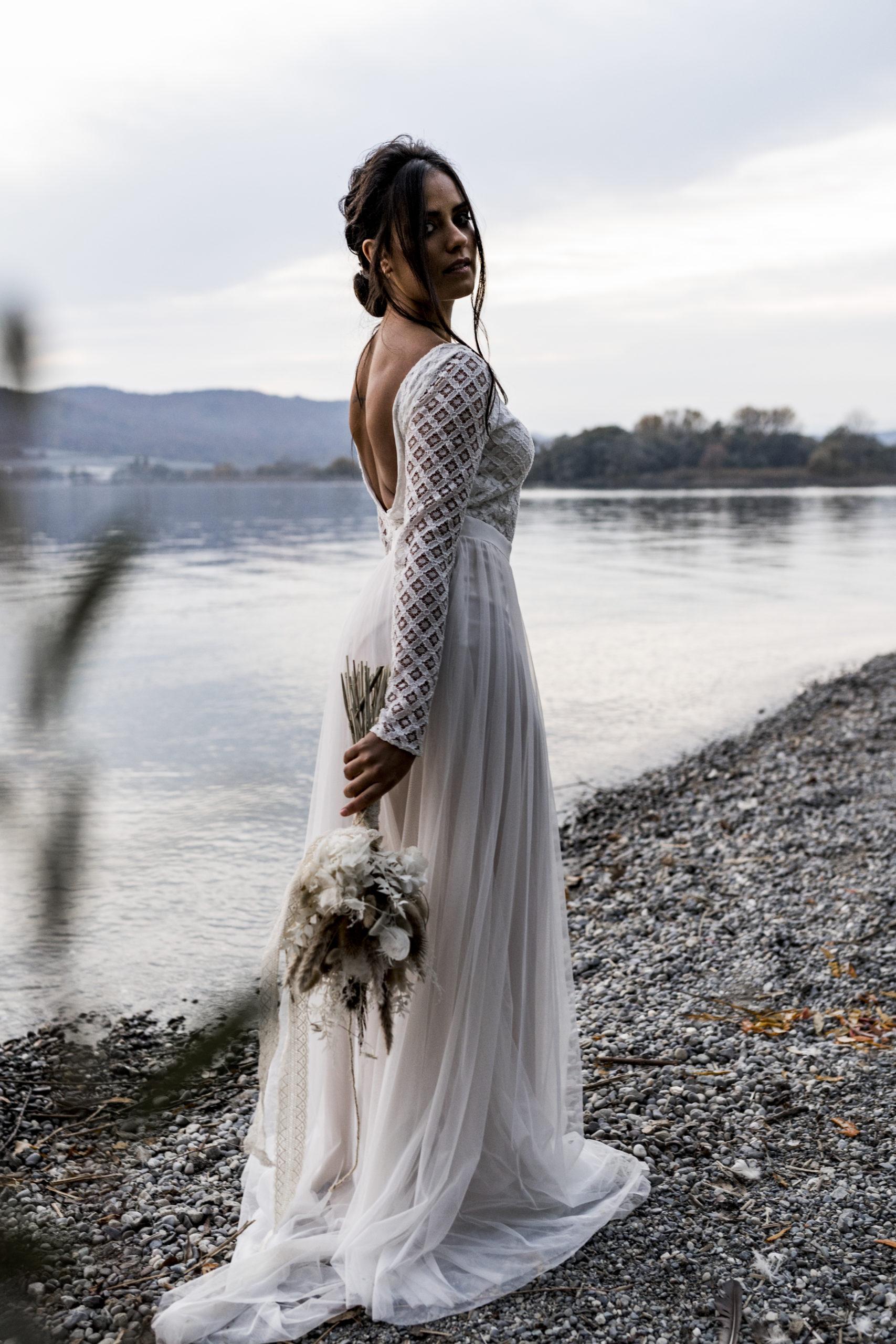 noni Brautmode, Styled Shoot am Bodensee, Model mit zweiteiligem Hochzeitskleid mit tiefem Rückenausschnitt und langem Tüllrock in Ivory mit Blush, Brautstrauss haltend und lachend