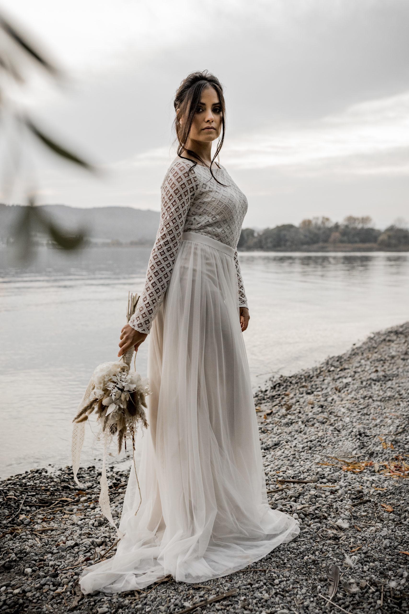 noni Brautmode, Styled Shoot am Bodensee, Model mit zweiteiligem Hochzeitskleid mit tiefem Rückenausschnitt und langem Tüllrock in Ivory mit Blush, Brautstrauss haltend